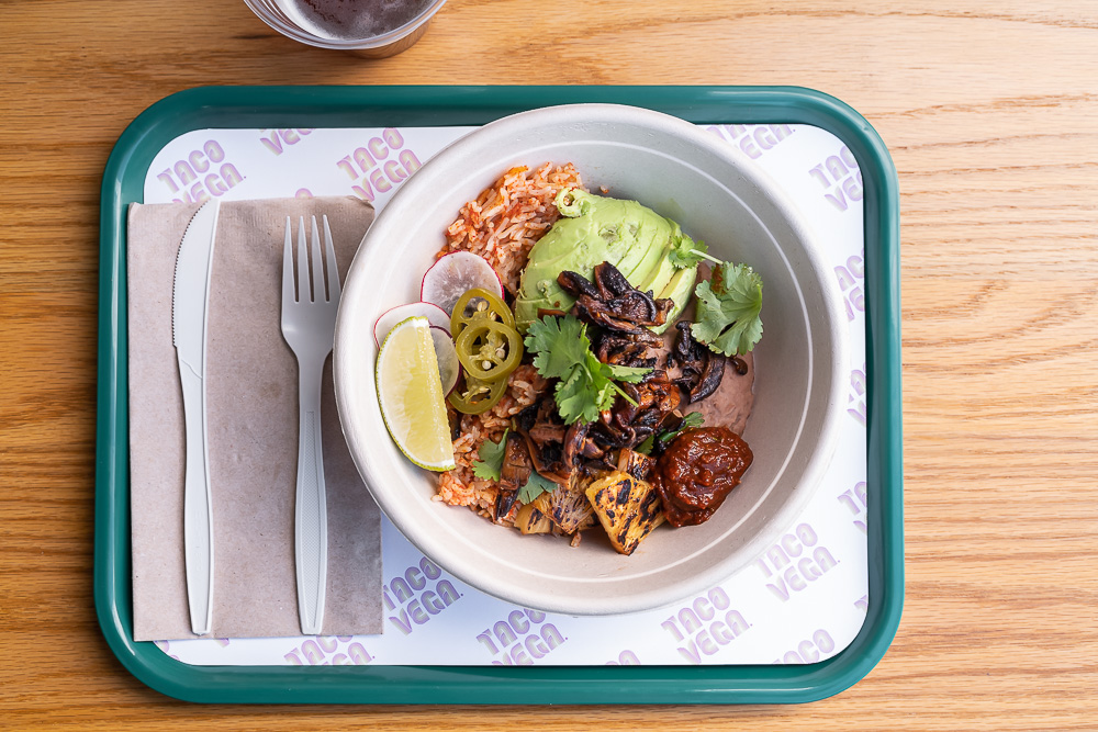 An overhead shot of a vegan bowl of Mexican food, from above, on a plastic tray.