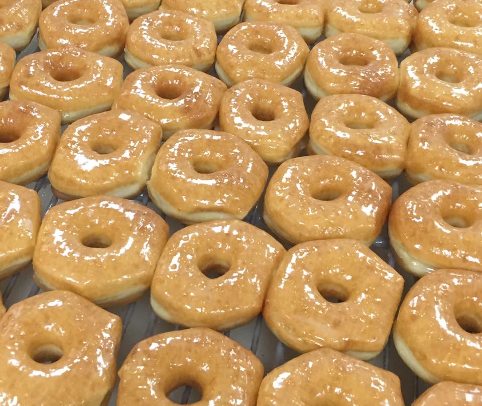 Row after row of plain, glazed doughnuts on a cooling rack