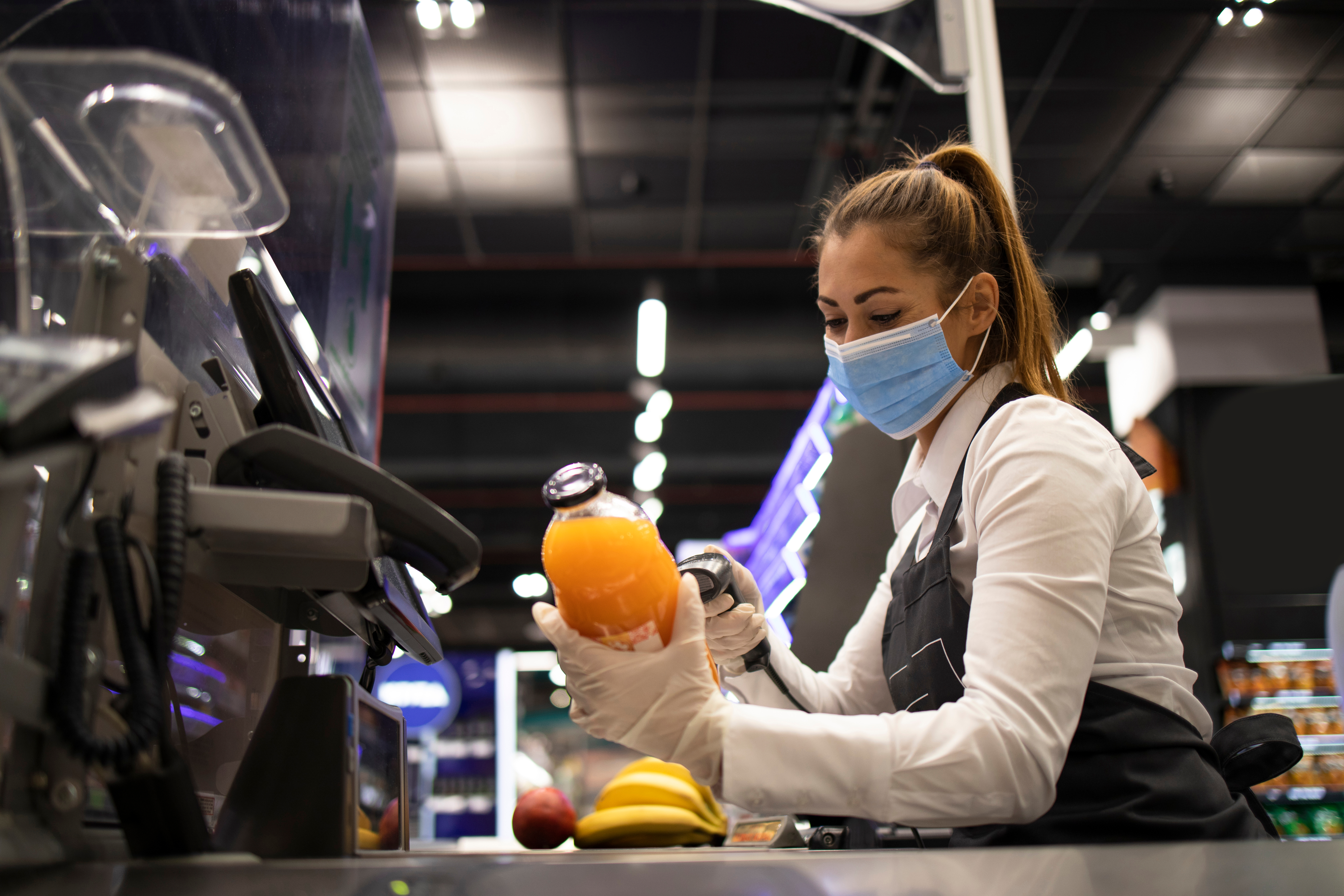 A female grocery store worker wearing a mask and gloves scans a bottled beverage at checkout.