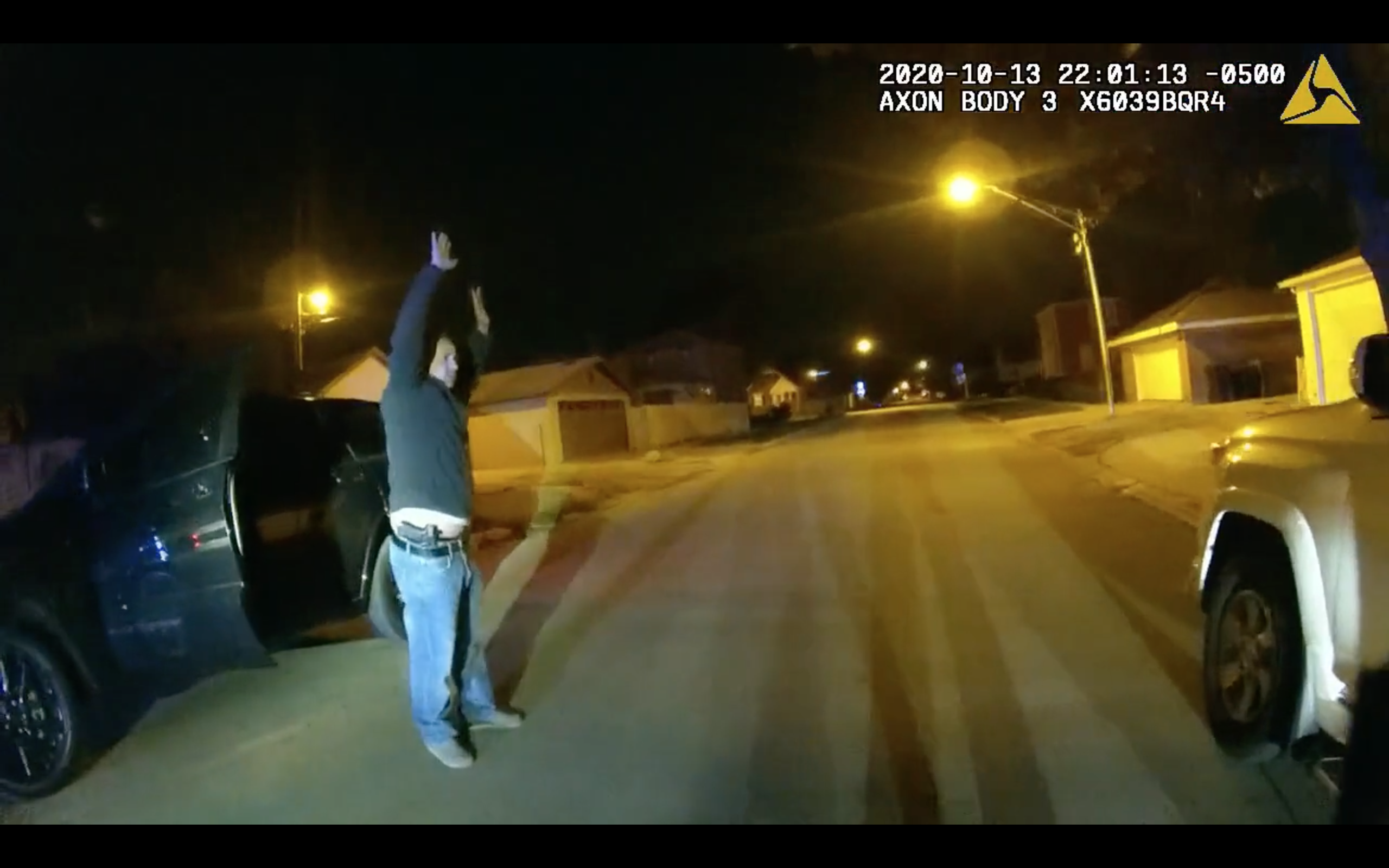 Off-duty Chicago Police Officer Joseph Cabrera raises his hands, showing a gun in his waistband, after he fired a round at a man on the Southwest Side last October.
