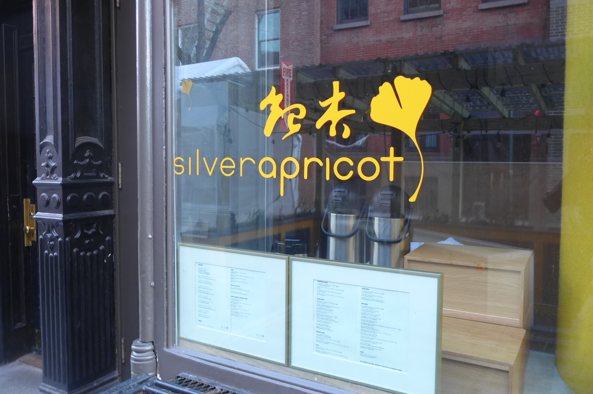 The name of the restaurant stenciled on the window in orange along with a single gingko leaf.