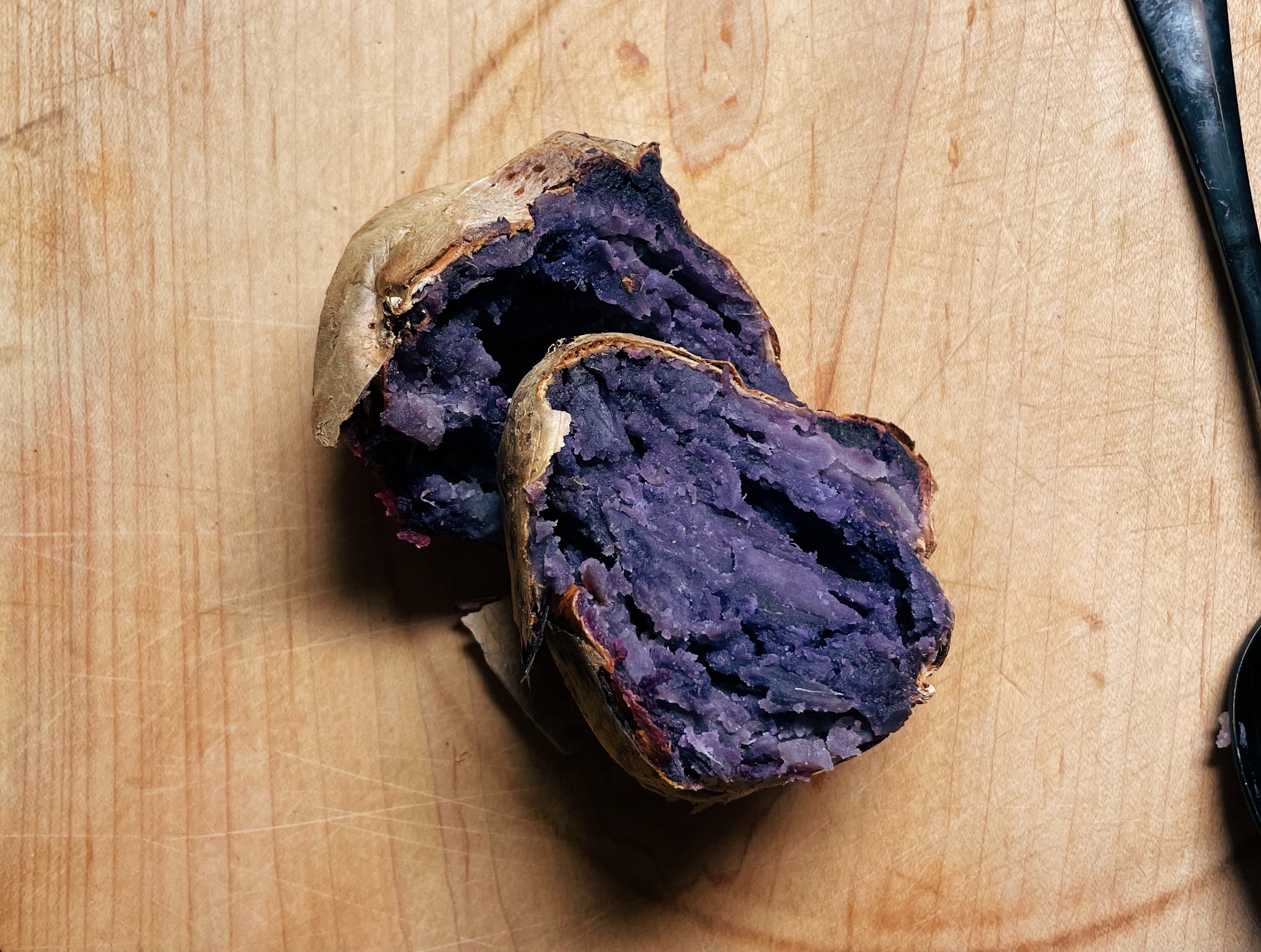 An overhead photo shows a purple baked sweet potato sliced lengthwise, sitting on a brown cutting board.