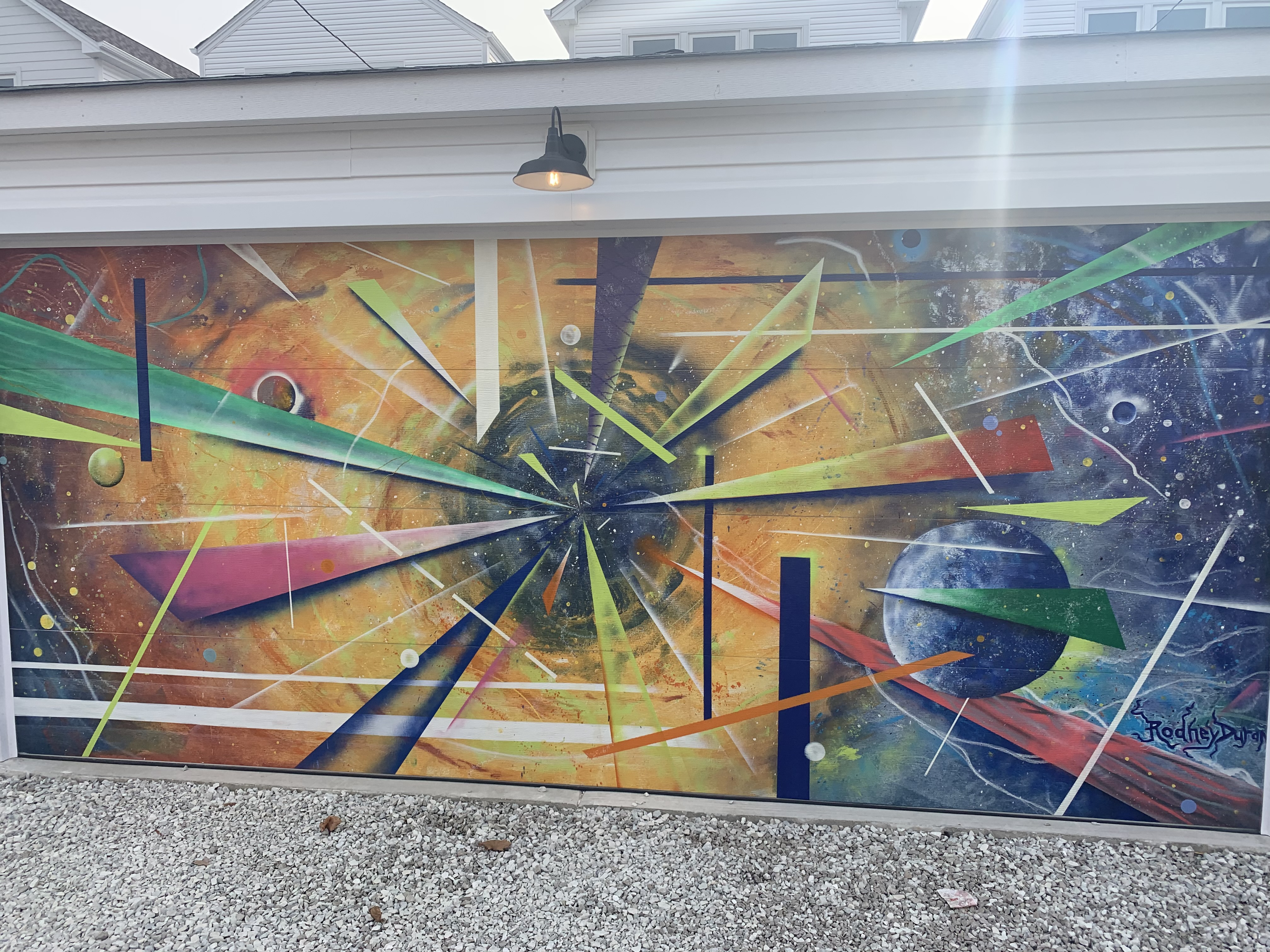 """This mural, by Uptown artist Rodney """"Hotrod"""" Duran, is one of 15 murals painted on garage doors in a single block on the Near West Side. Duran says he's """"really into astronomy and space and time"""" and was trying to get across that, if everyone looked toward Jupiter's moon Callisto, we could all be """"feeling the same beauty."""""""