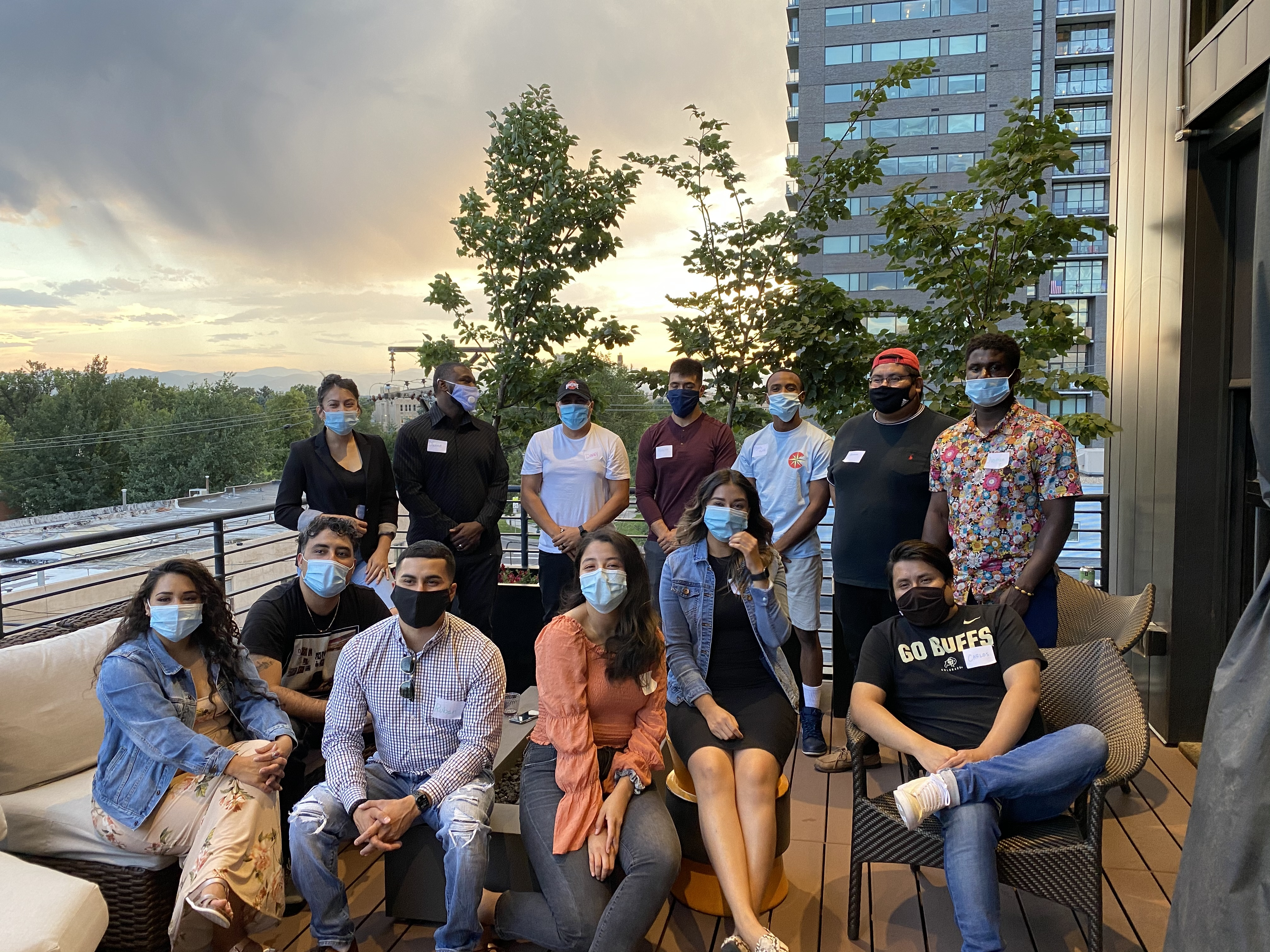 A group of young Denver Public Schools alumni wearing masks gather for a photo.