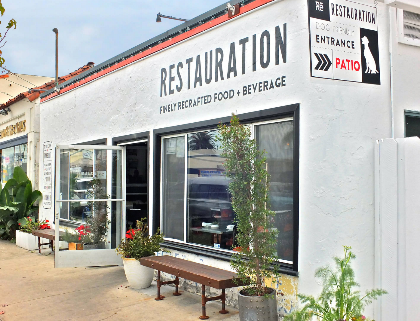 A white Spanish stucco restaurant shown from the outside at daytime.