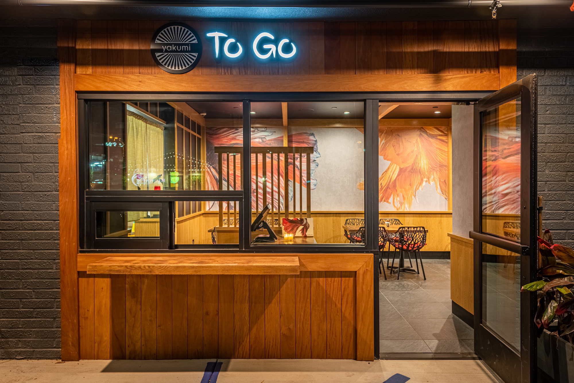A takeout/to-go window wrapped in wood for a new sushi restaurant, at night.