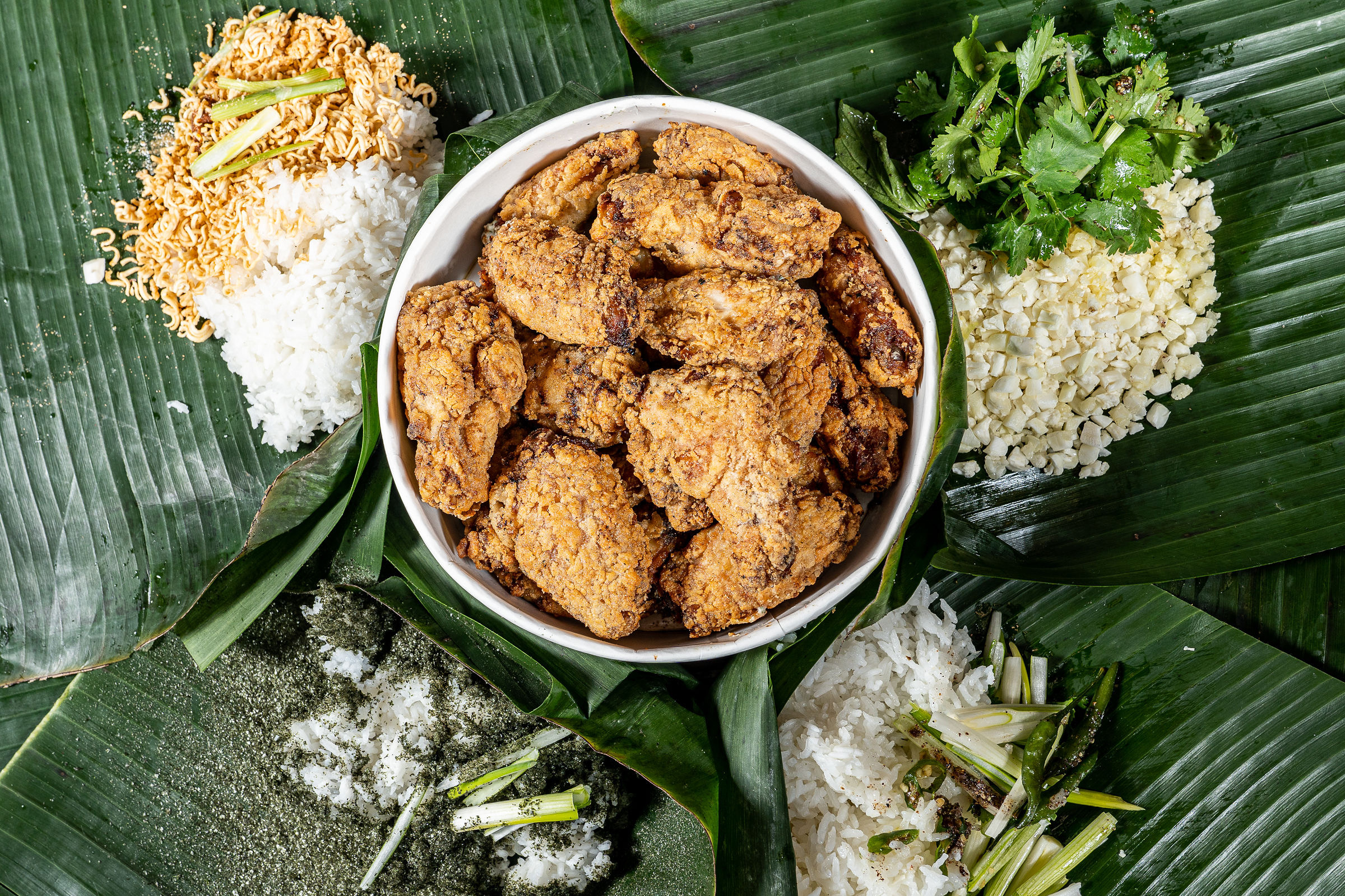 A bowl of fried chicken is surrounded by banana leaves, topped with rice, at Prey & Tell