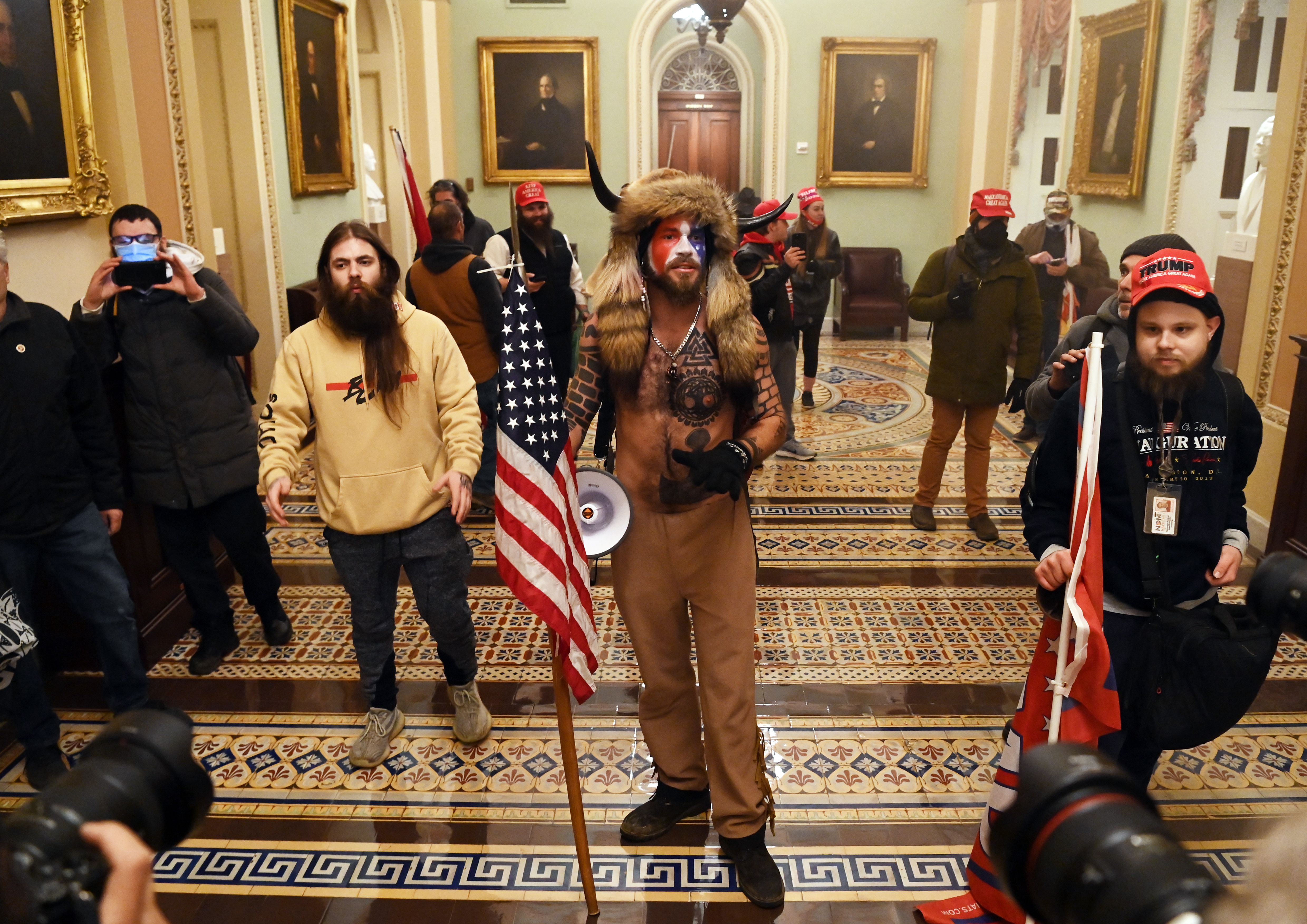Members of the mob that broke into the US Capitol stand holding flags in a Capitol hallway.