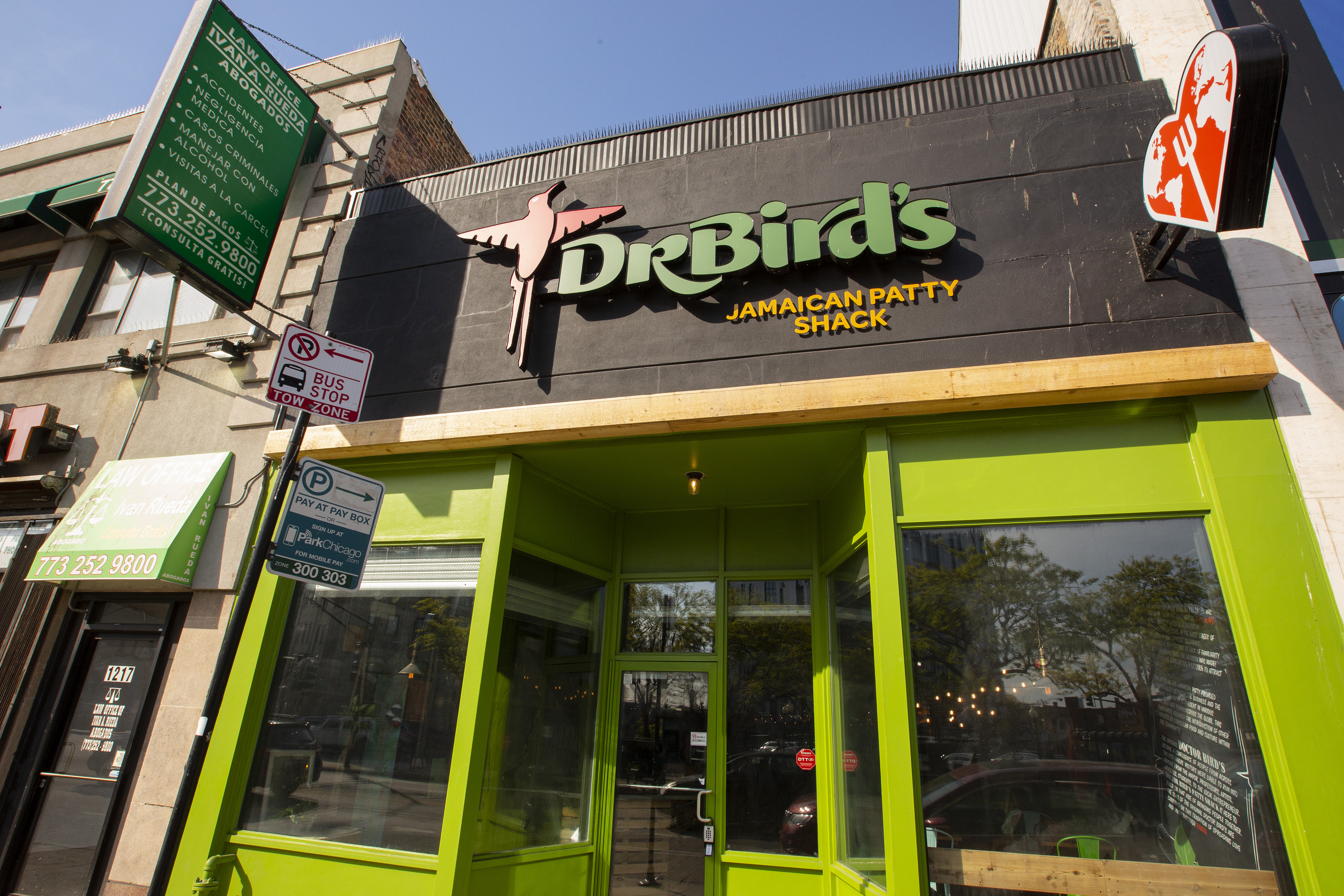 """A storefront restaurant exterior painted bright green with a big sign that reads """"Dr. Bird's Jamaican Patty Shack."""""""