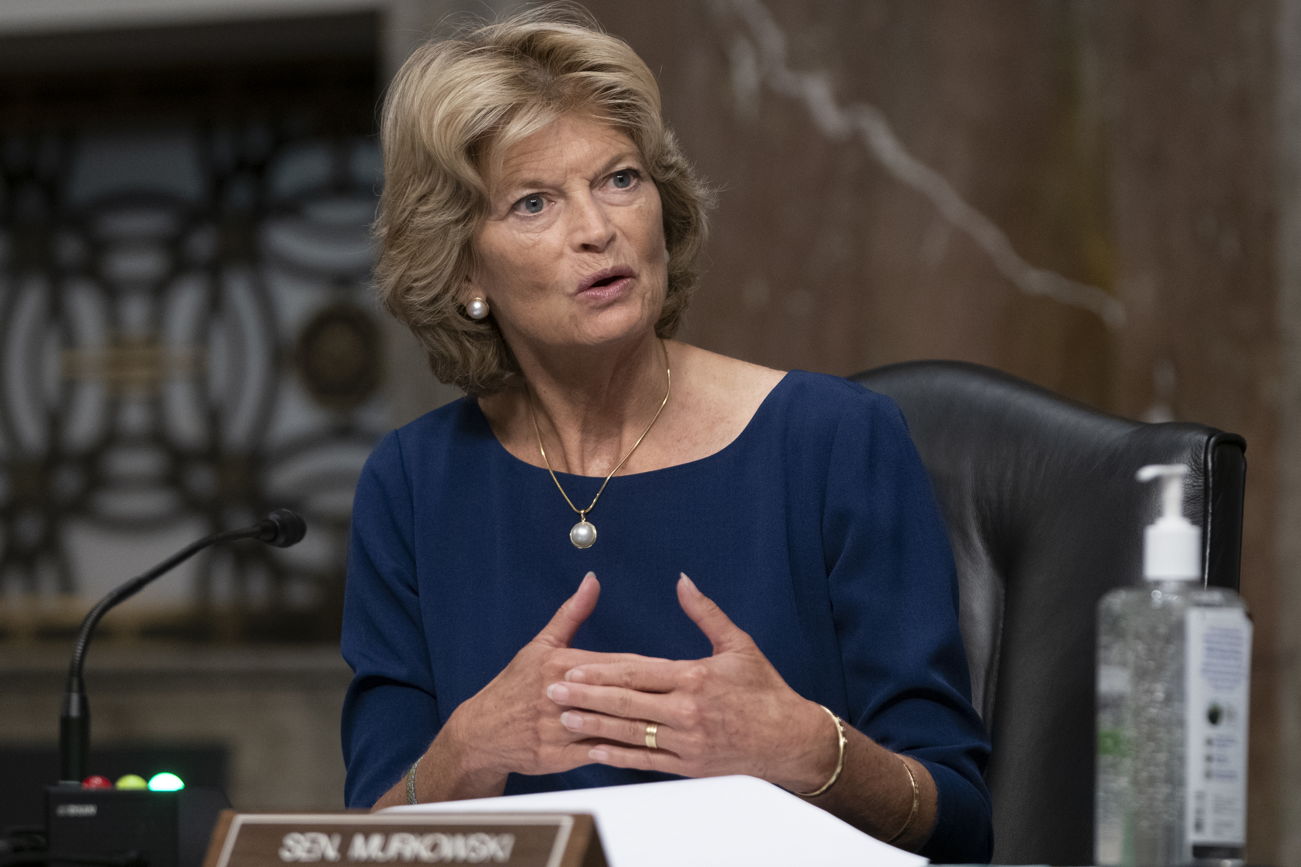Murkowski, seated in a blue dress, speaks into a microphone without a mask. A large bottle of hand sanitizer is to her left.