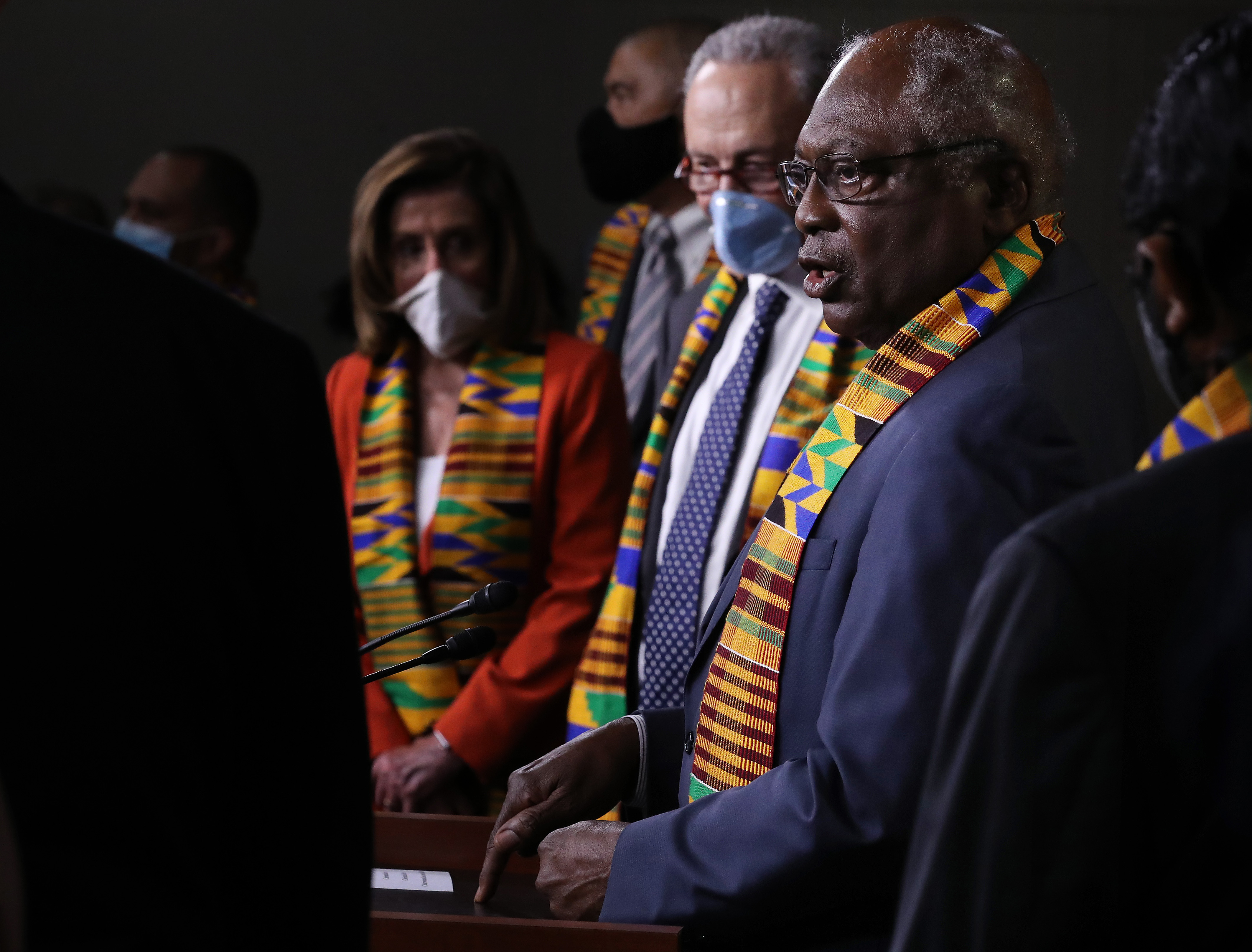 Clyburn, in a blue suit, and with a kente cloth stole around his neck, speaks as Schumer — in a navy suit — and Pelosi — in a red suit — look on. Both Pelosi and Schumer are wearing masks, and both also have on kente cloth stoles.
