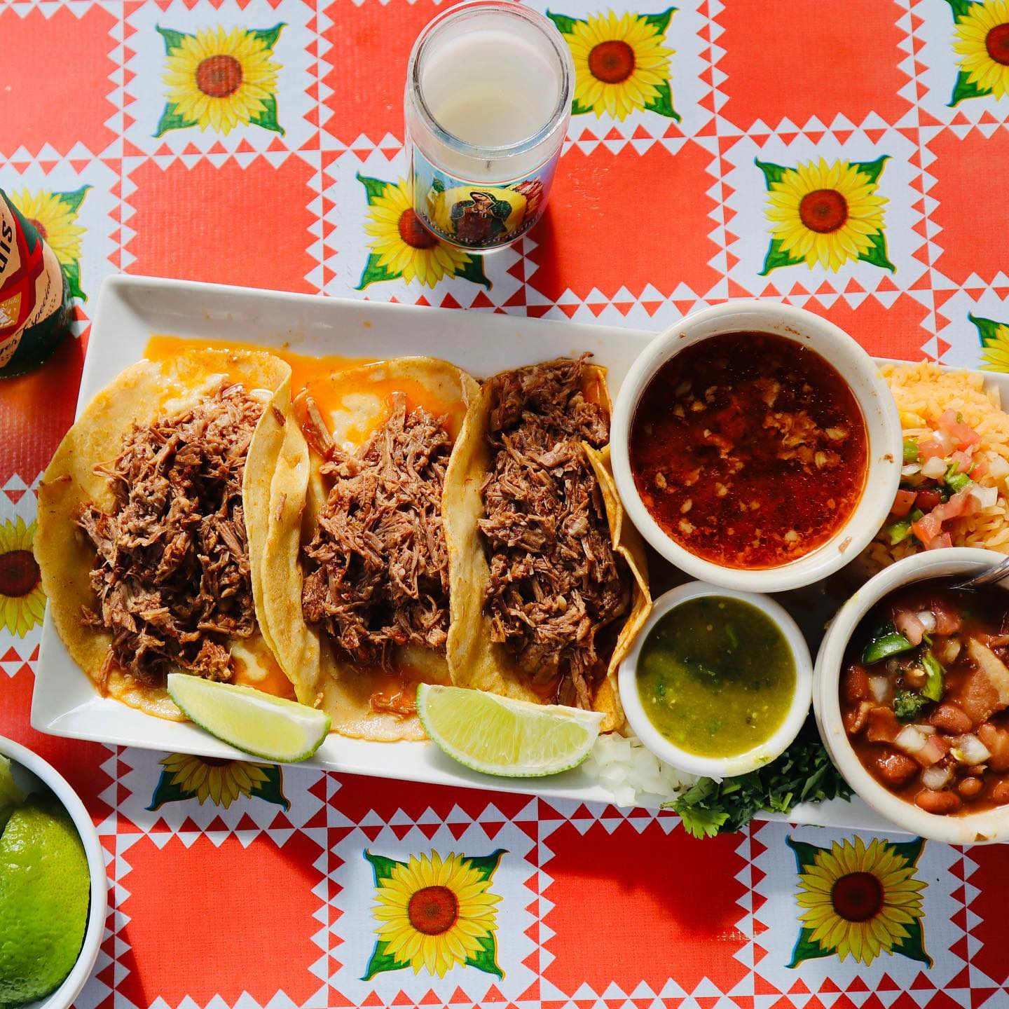 Overhead shot of three tacos with limes on a printed red tablecloth with sunflowers