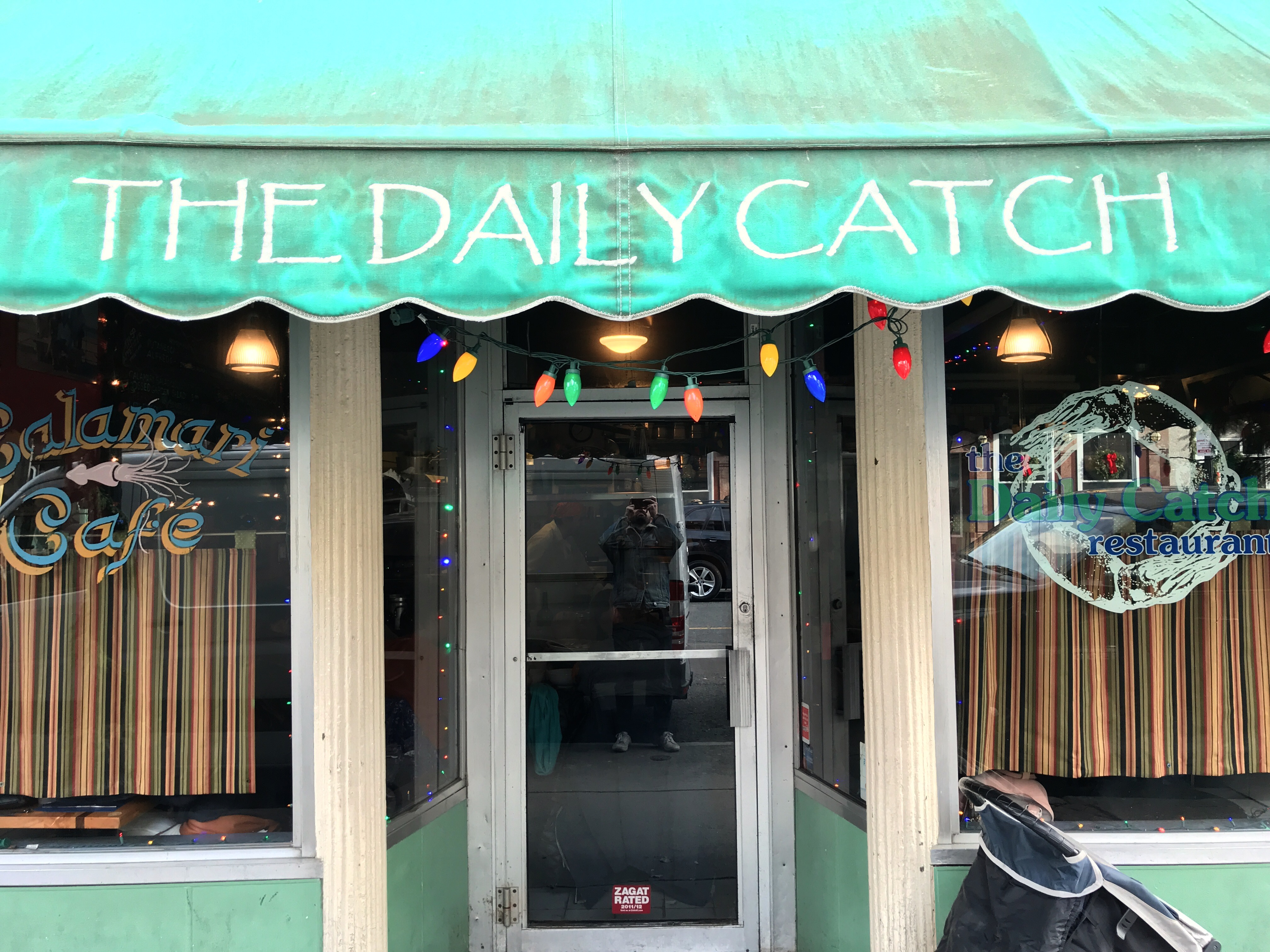 """A weathered green awning with the words""""The Daily Catch"""" written on it in white in Boston's North End neighborhood"""