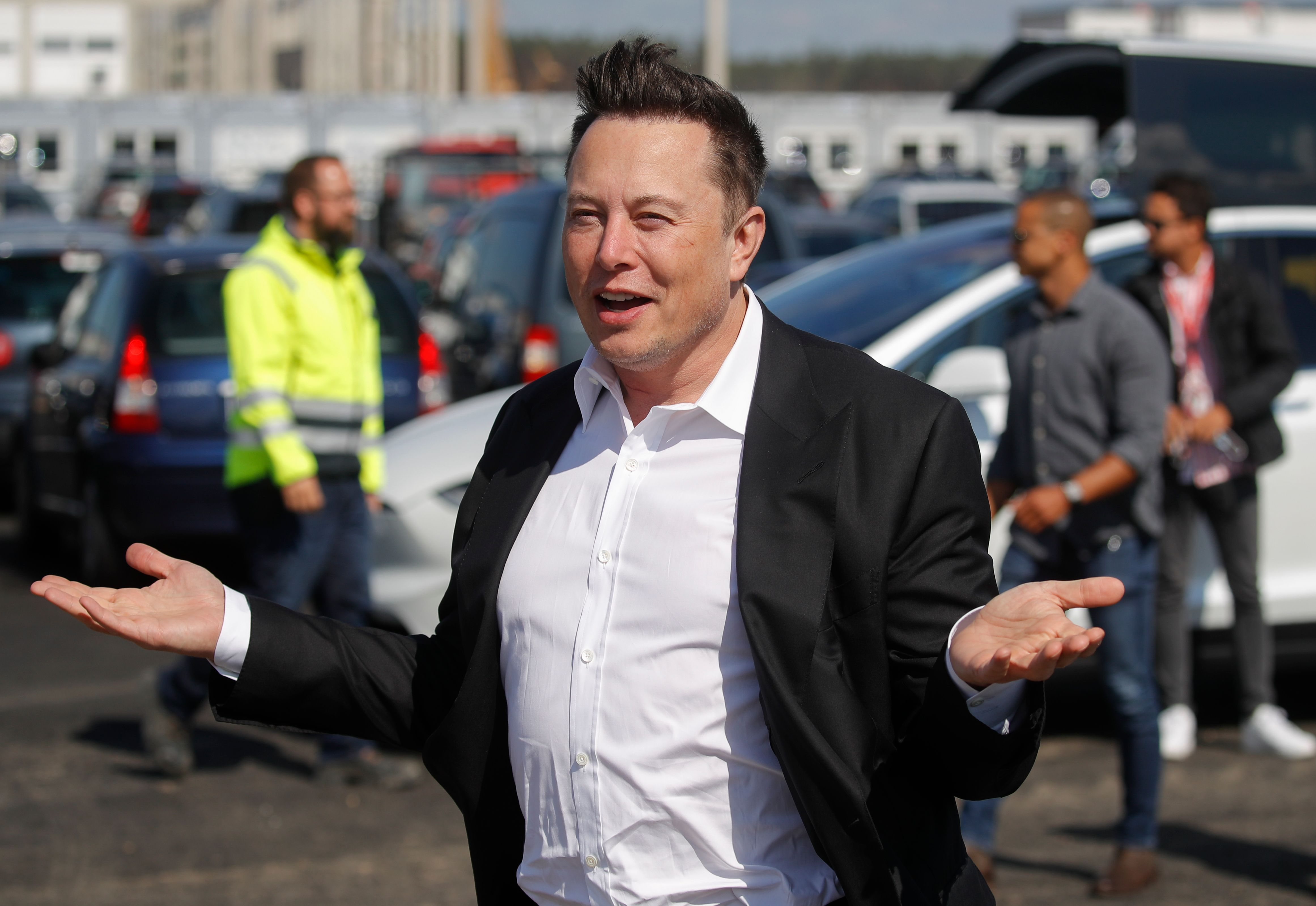 Elon Musk shrugs his arms in a photo
