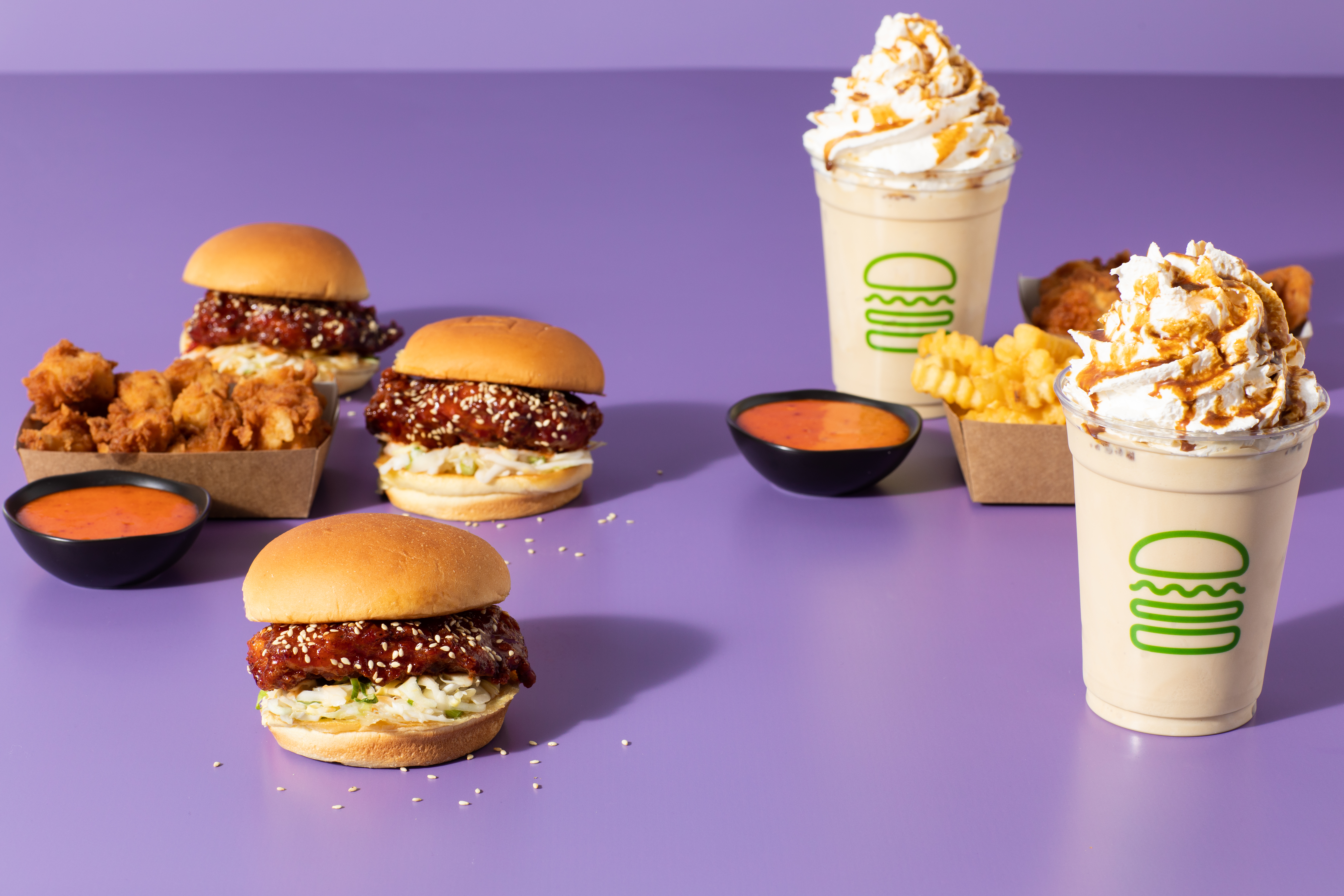 Fried chicken sandwiches, nuggets, fries, and two milkshakes laid out with a purple background