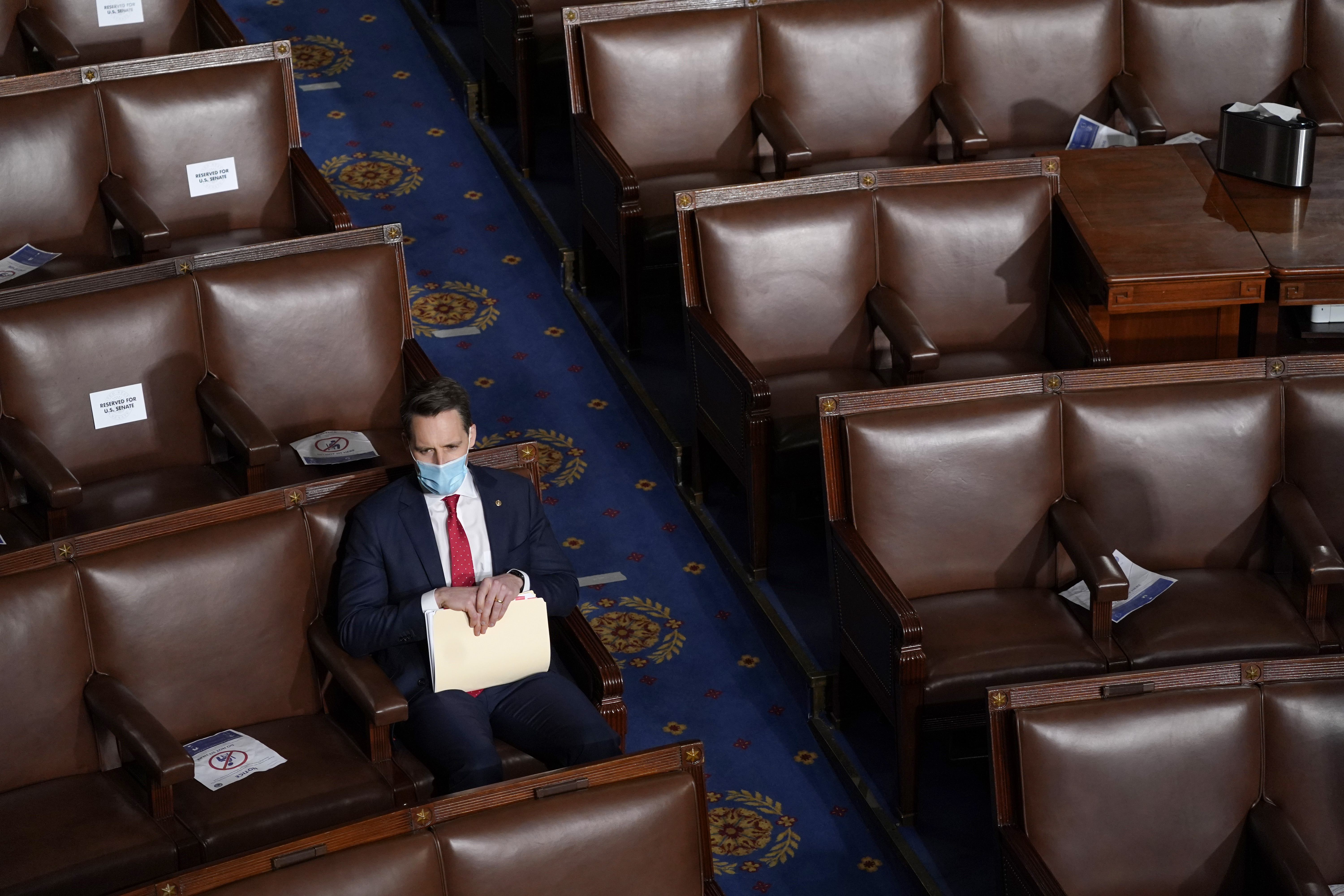 Senator Josh Hawley sitting in a seat in Congress surrounded by empty seats.