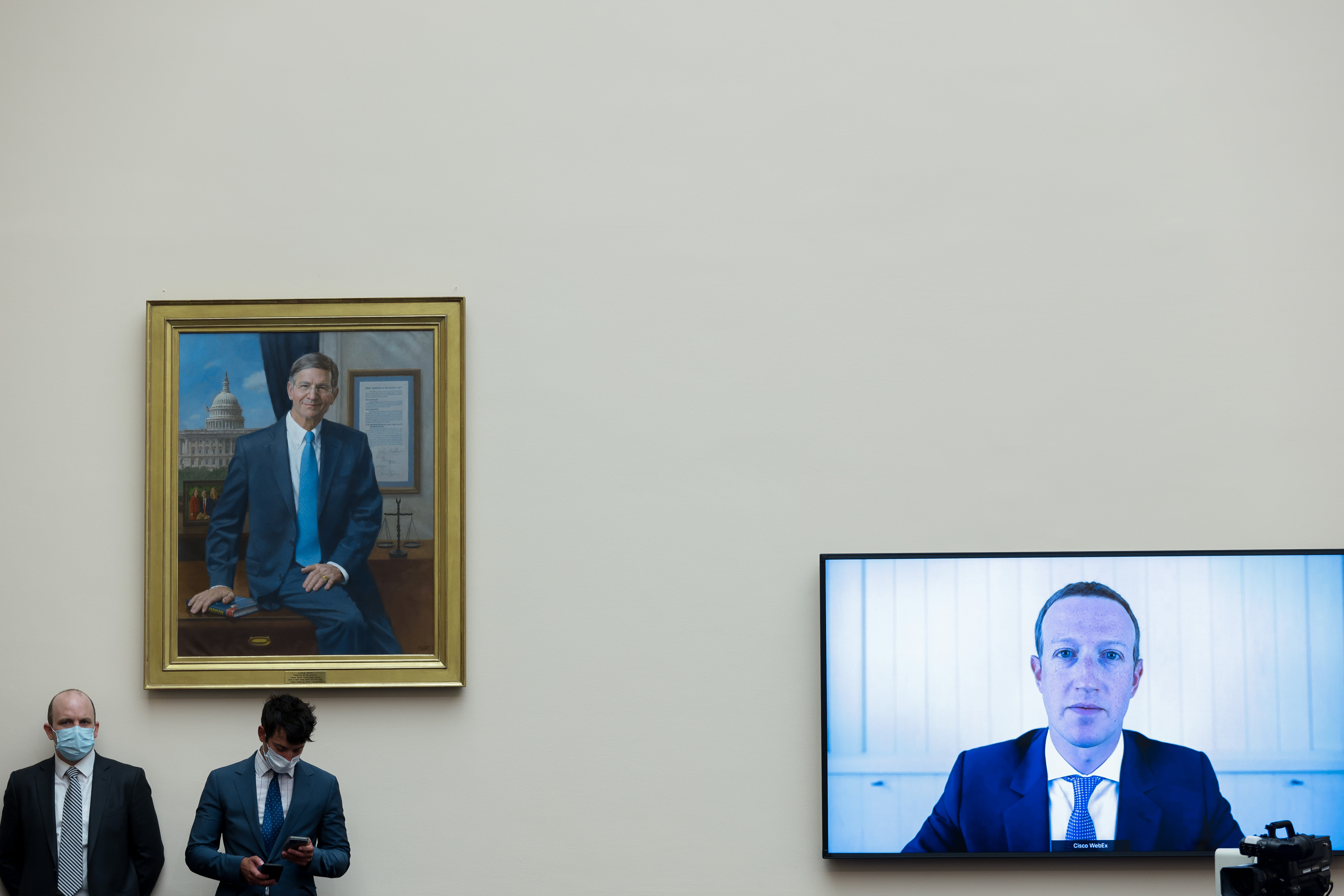 Mark Zuckerberg on a television screen speaking before Congress