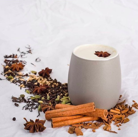Chai matcha latte with dried cinnamon sticks, star anise, and other herbs surrounding a off white, handleless mug. A star anise floats on top of the latte drink