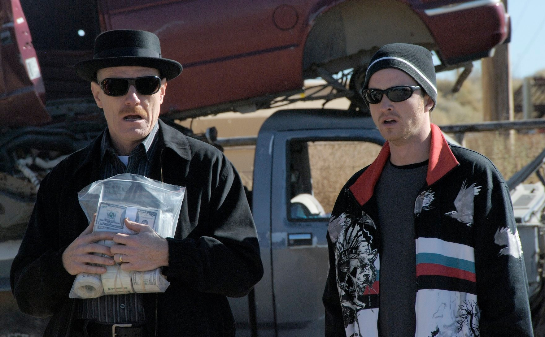 Bryan Cranston, portraying Walter White, stands on the left holding a plastic bag full of cash. Aaron Paul, portraying Jesse Pinkman, stands to the right, wearing a black, red, and white jacket.