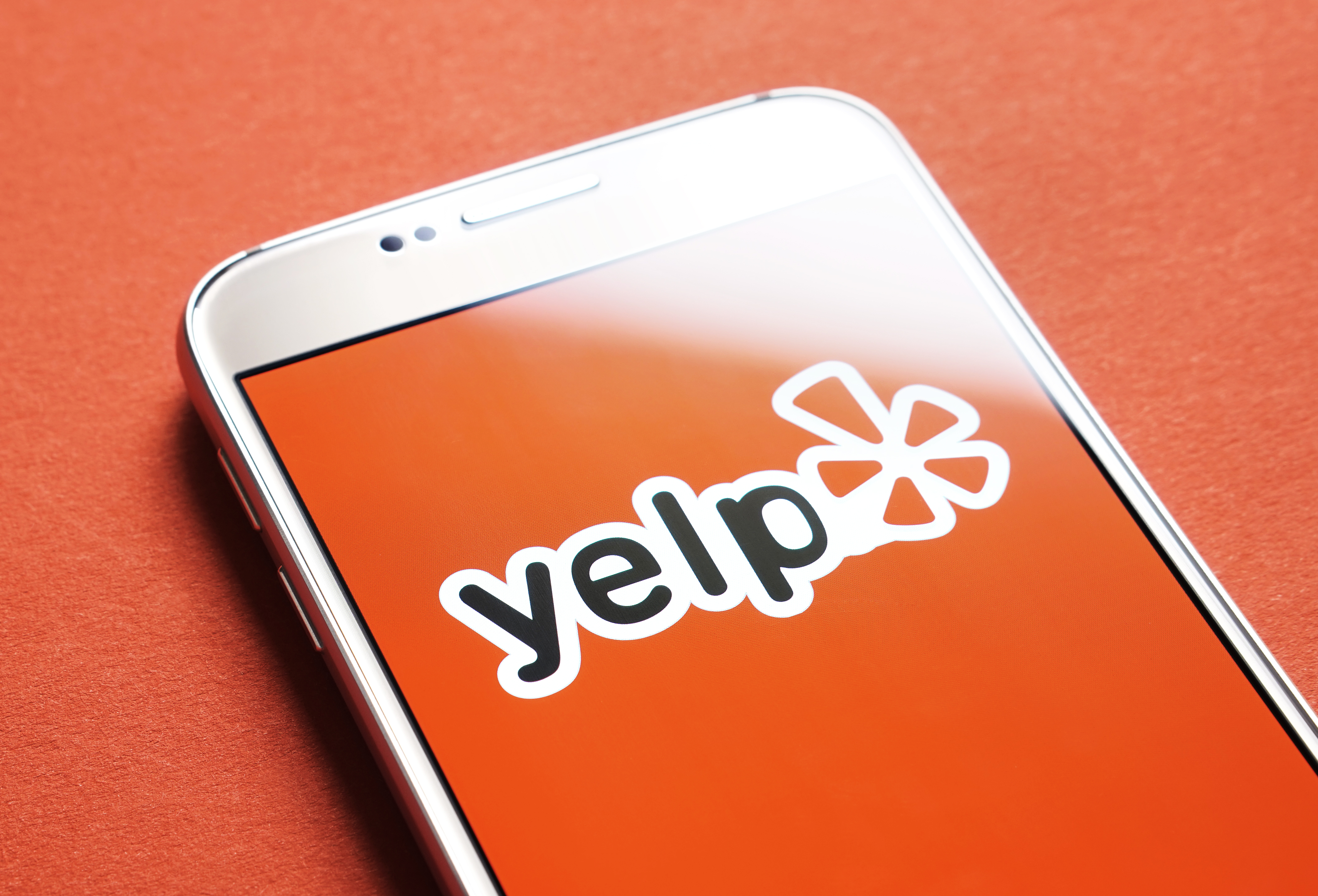 Yelp red screen and logo on a smartphone.