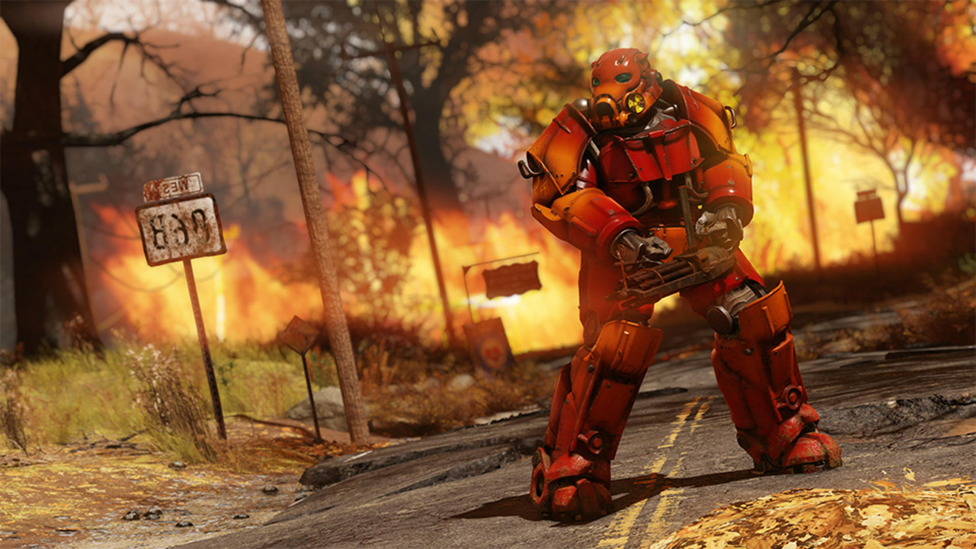 Fallout 76 - a power armor wearing soldier with a mini gun poses menacingly. His armor is painted red, and a forest fire rages in the background.