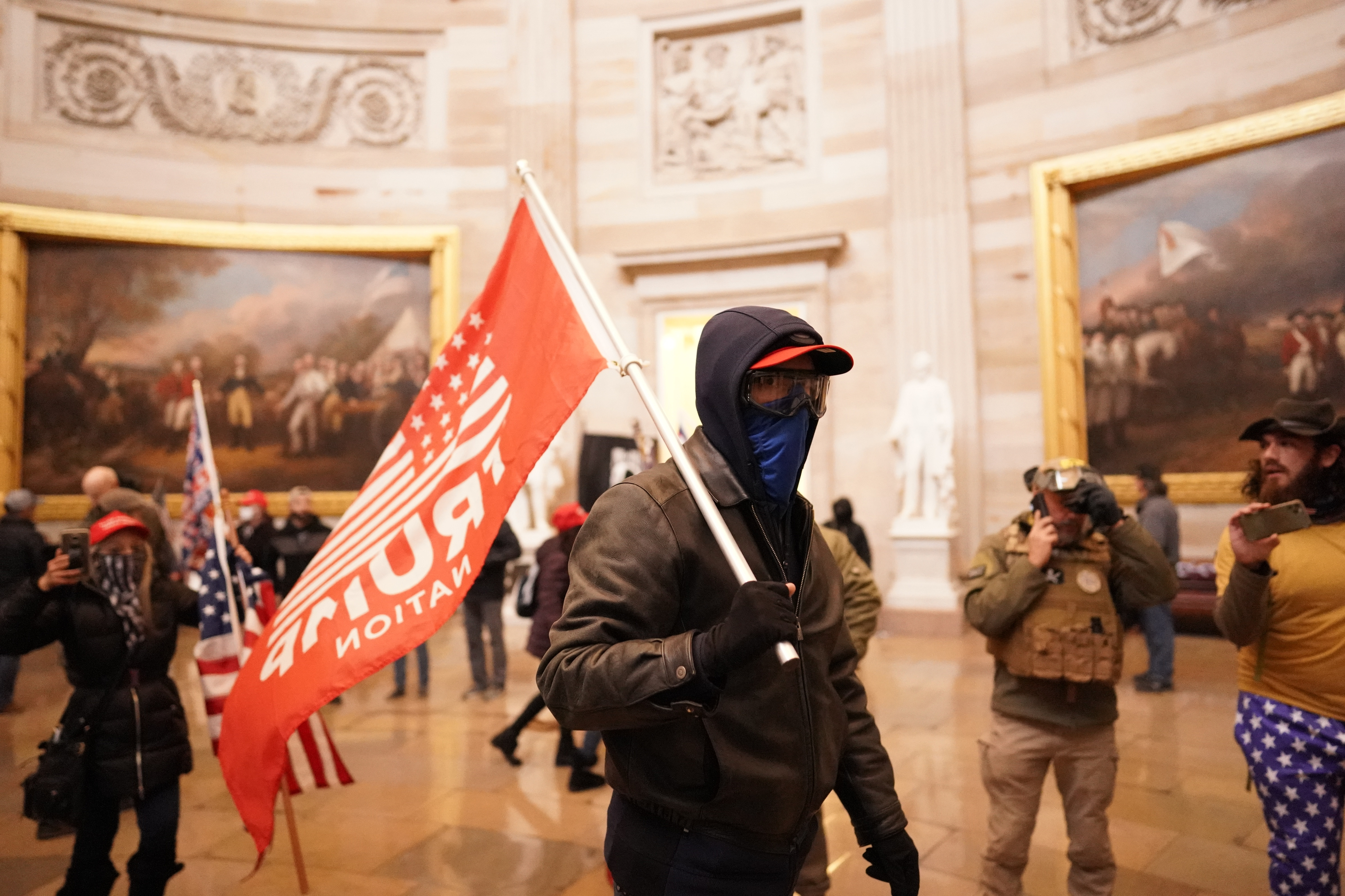 Protesters in a chamber of the Capitol in Washington, DC, one holding a Trump flag.