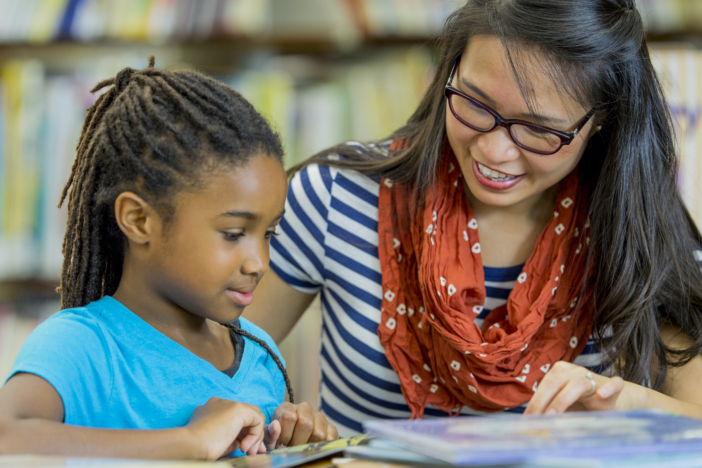 A teacher is reading books with an elementary age girl in the library.