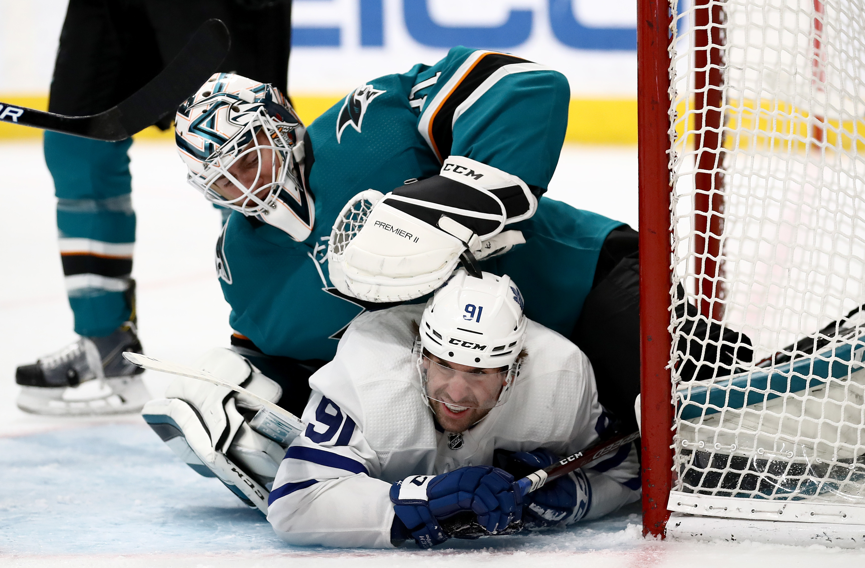 John Tavares #91 of the Toronto Maple Leafs collides with Martin Jones #31 of the San Jose Sharks at SAP Center on March 03, 2020 in San Jose, California.