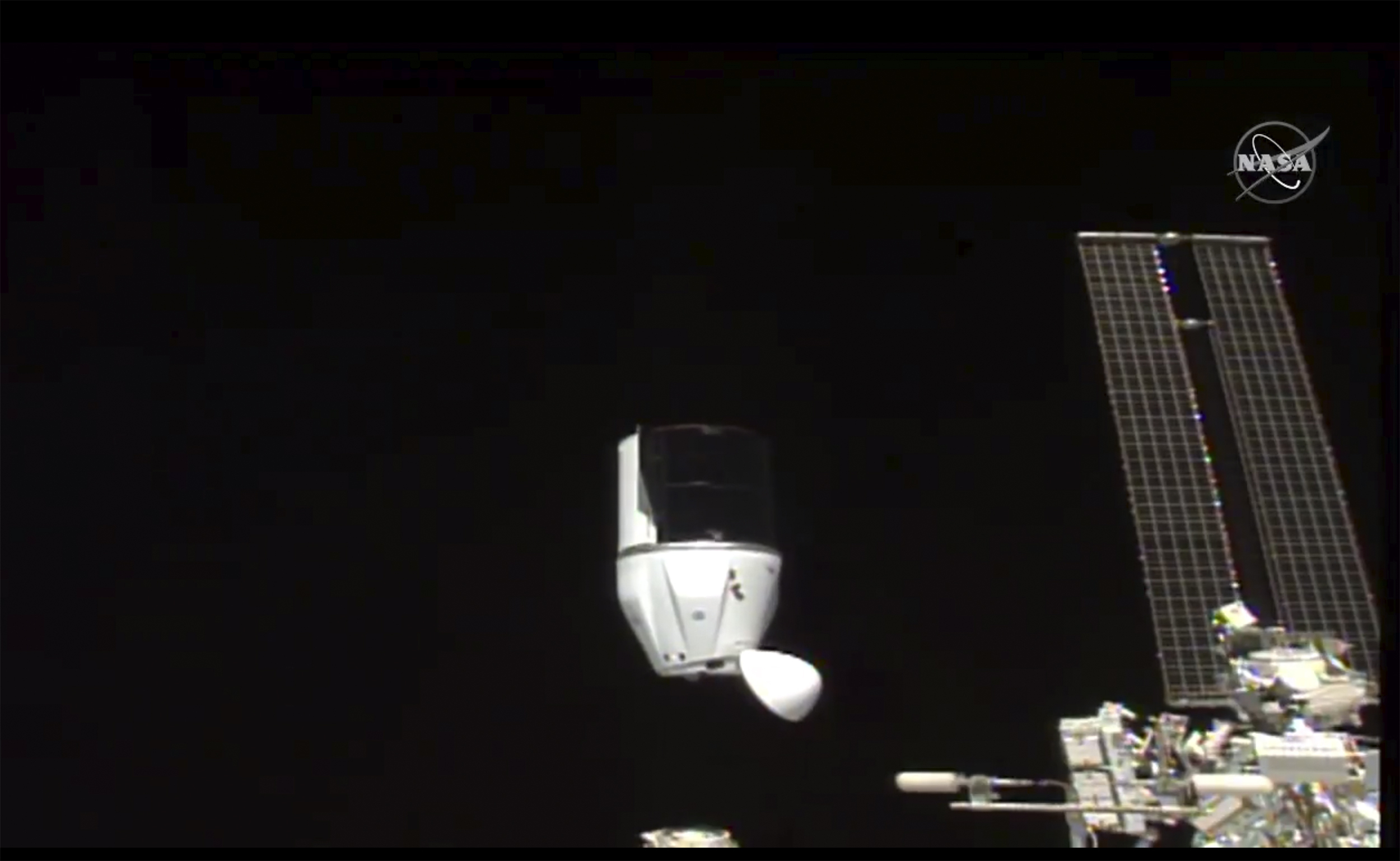 This photo provided by NASA shows SpaceX's Dragon undocking from International Space Station on Tuesday, Jan. 12, 2021. SpaceX's Dragon cargo capsule undocked with 12 bottles of Bordeaux wine and hundreds of snippets of Merlot and Cabernet Sauvignon vines.