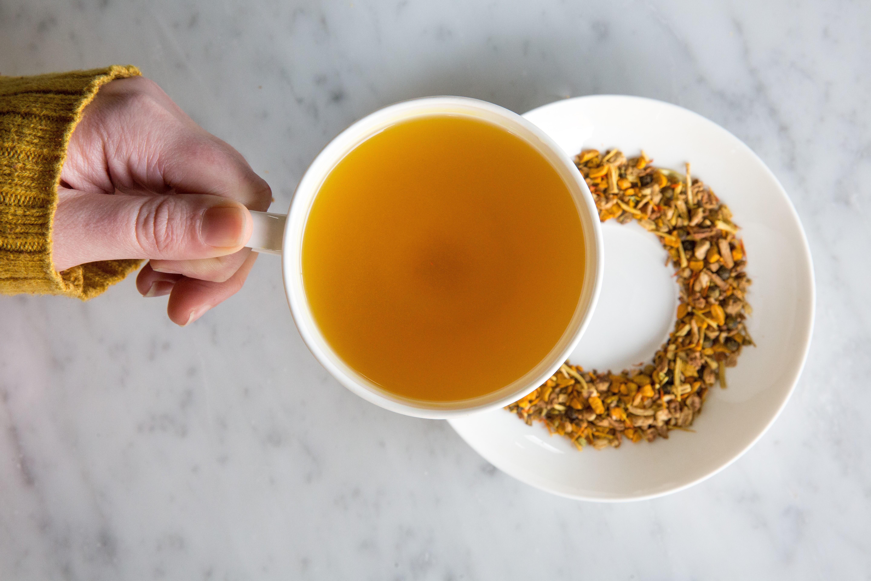 A hand holds a mug of orange-brown tea over a floral-looking pile of loose-leaf tea
