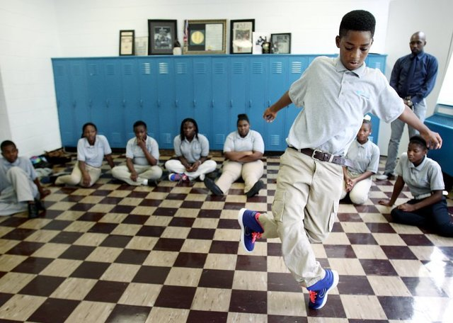 Eighth-grade boy in pale-blue shirt and beige trousers dances in front of classmates seated on a tile floor in front of lockers.