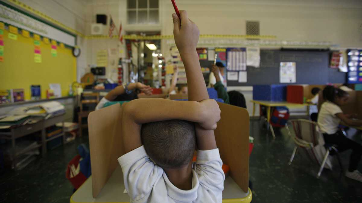 Student raising hand in class.