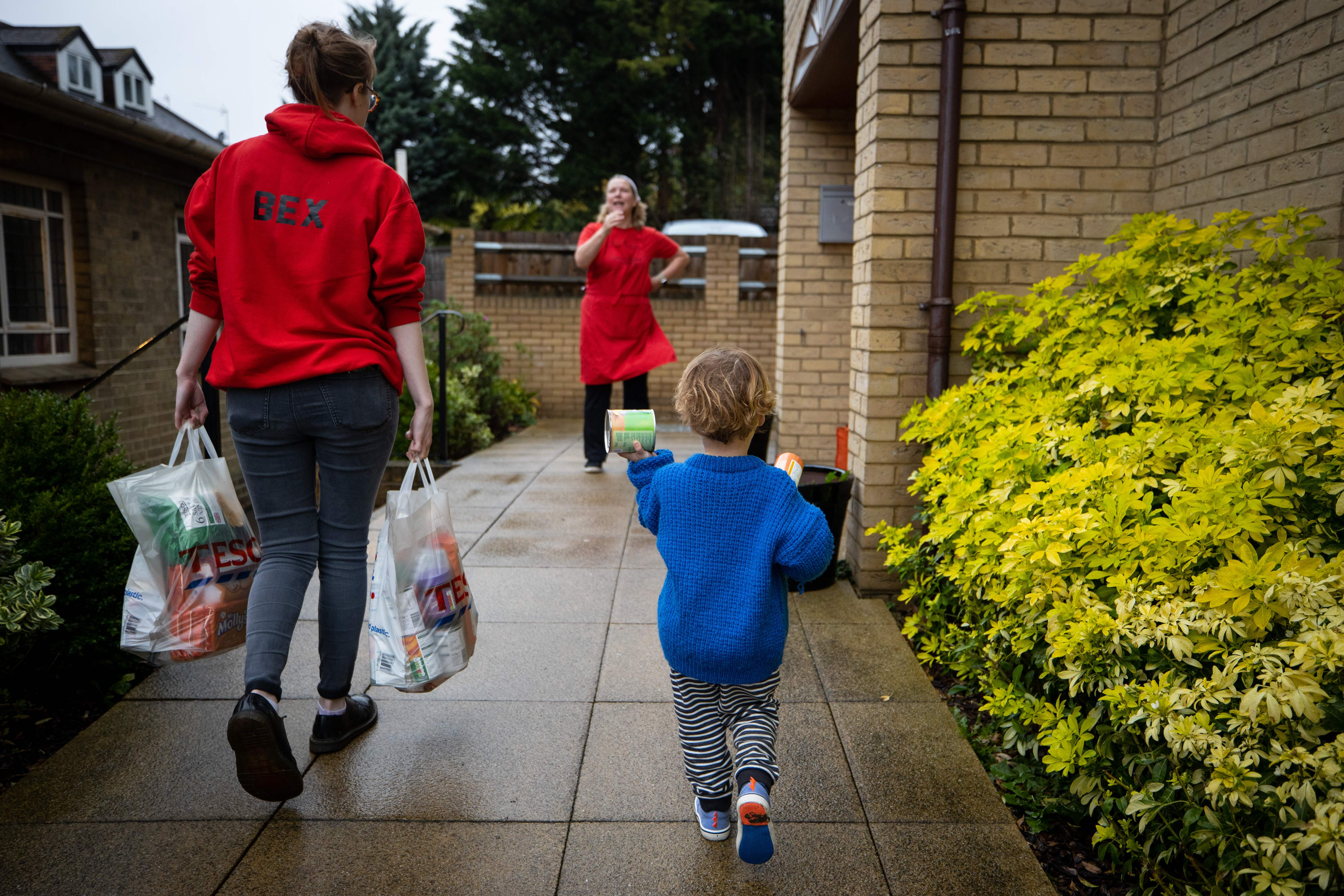 A food bank volunteer carries food parcels in a carrier bag up a driveway, alongside a child