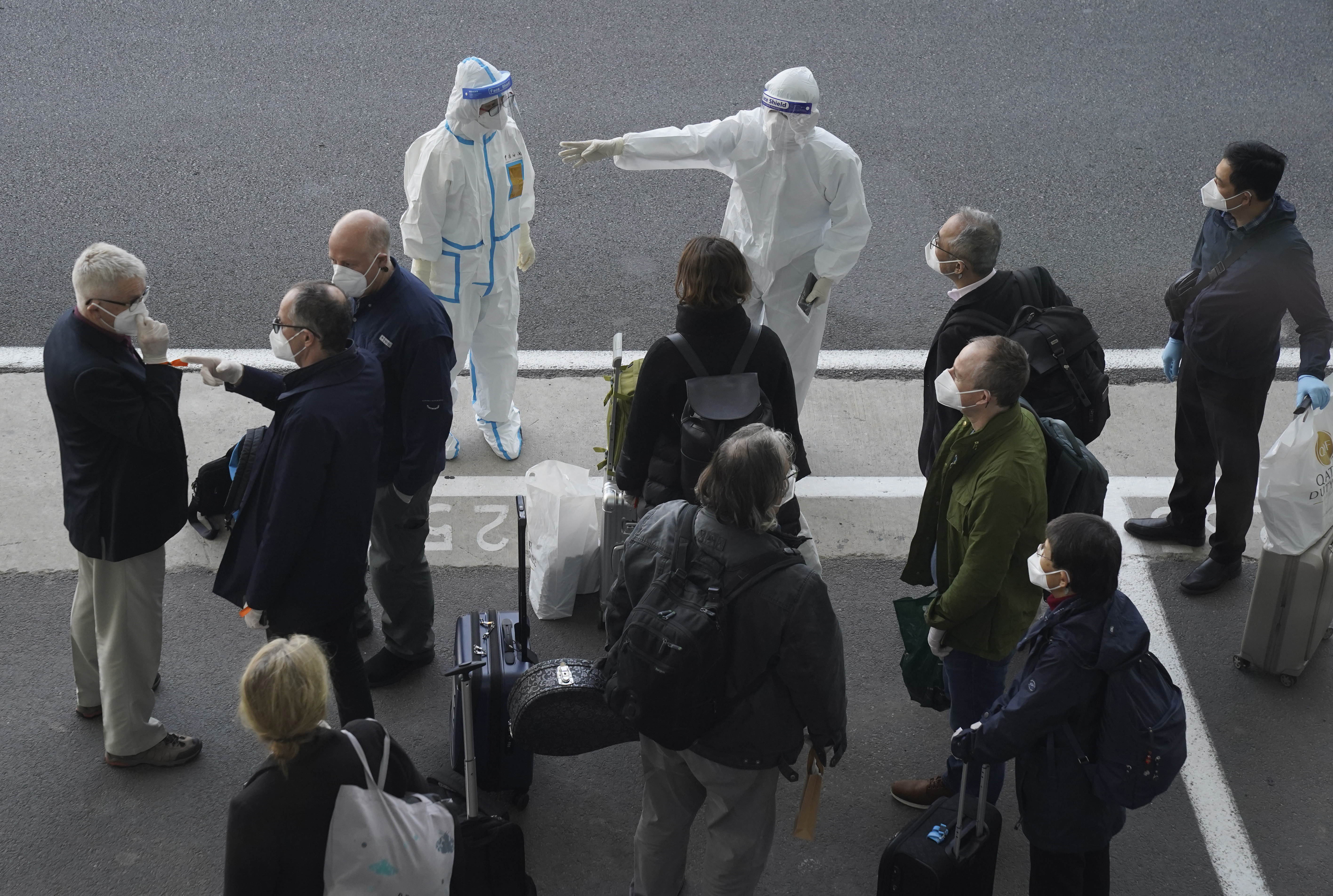 A worker in protective coverings directs members of the World Health Organization (WHO) team on their arrival at the airport in Wuhan in central China's Hubei province on Thursday, Jan. 14, 2021.