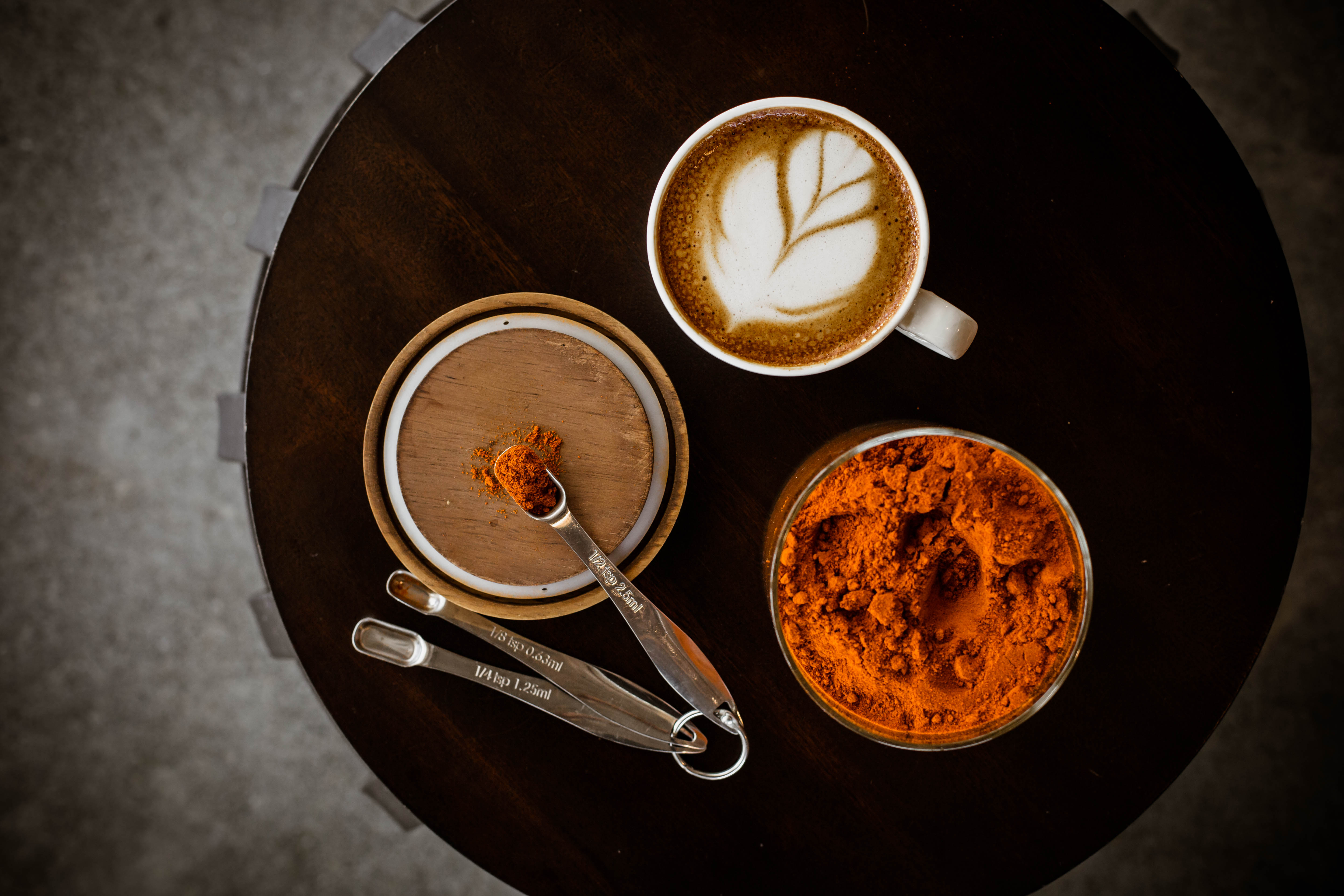 Topdown view of a berbere latte from Boona Boona with two cups nearby containing spices and other ingredients