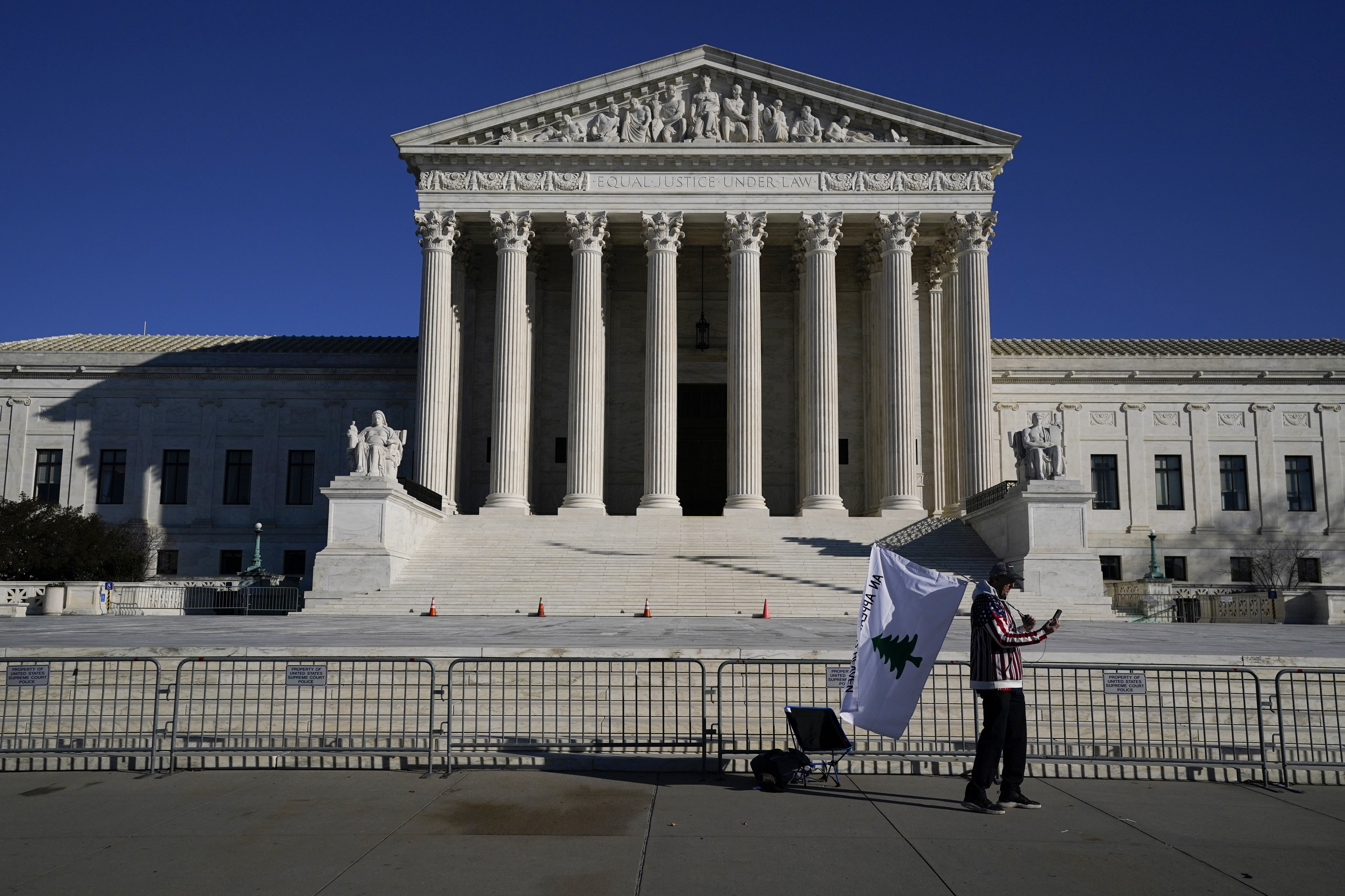 A person walks by newly-placed barricades around the Supreme Court Building, the day after violent protesters loyal to President Donald Trump stormed the U.S. Congress in Washington, Thursday, Jan. 7, 2021.