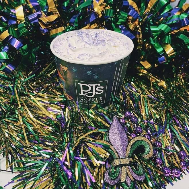 a latte topped with whipped cream and purple sugar, surrounded by mardi gras themed tinsel and fleur de lis decor