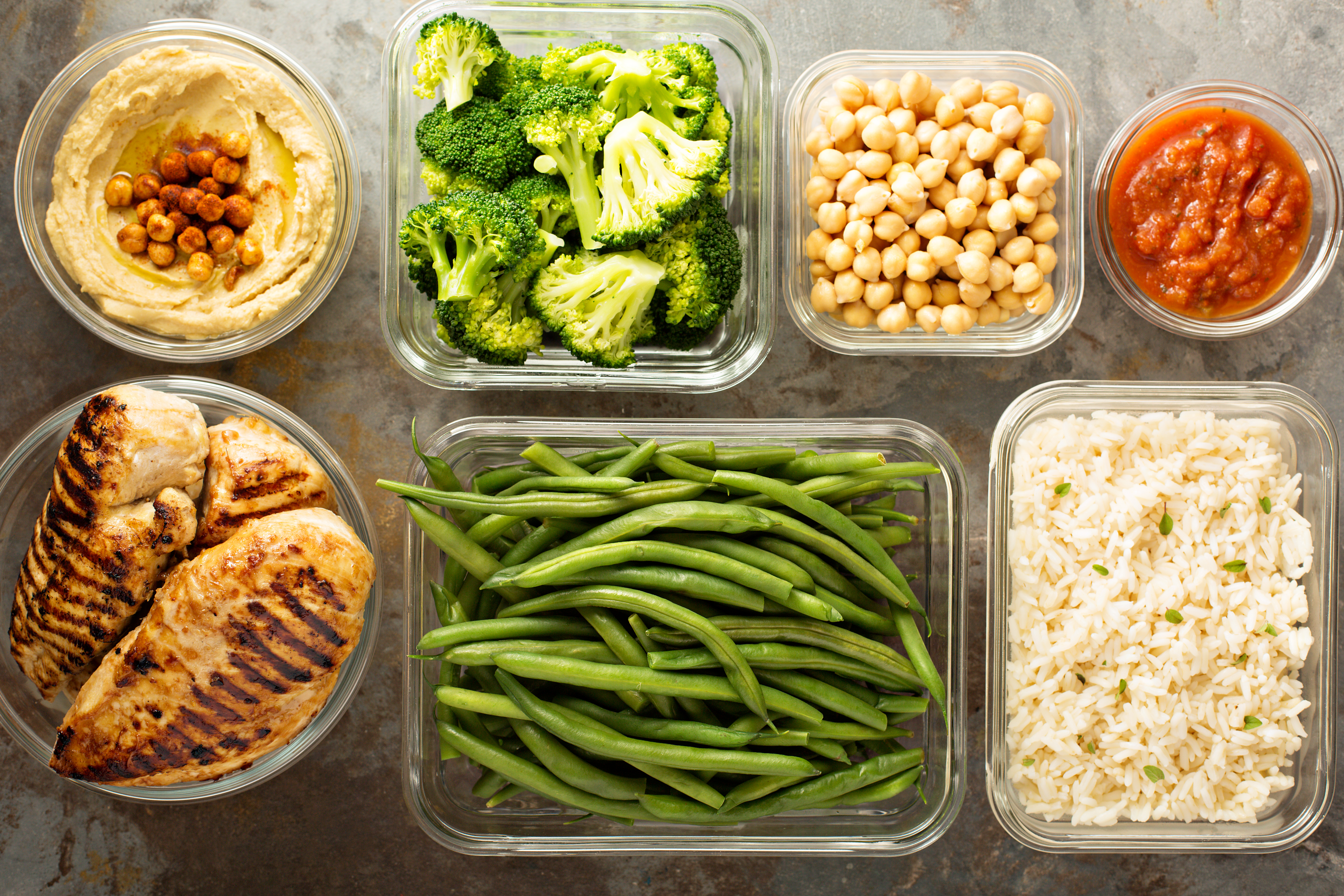An overhead photo shows seven glass containers, some containing cooked vegetables, one containing brown rice, and another containing grilled chicken.