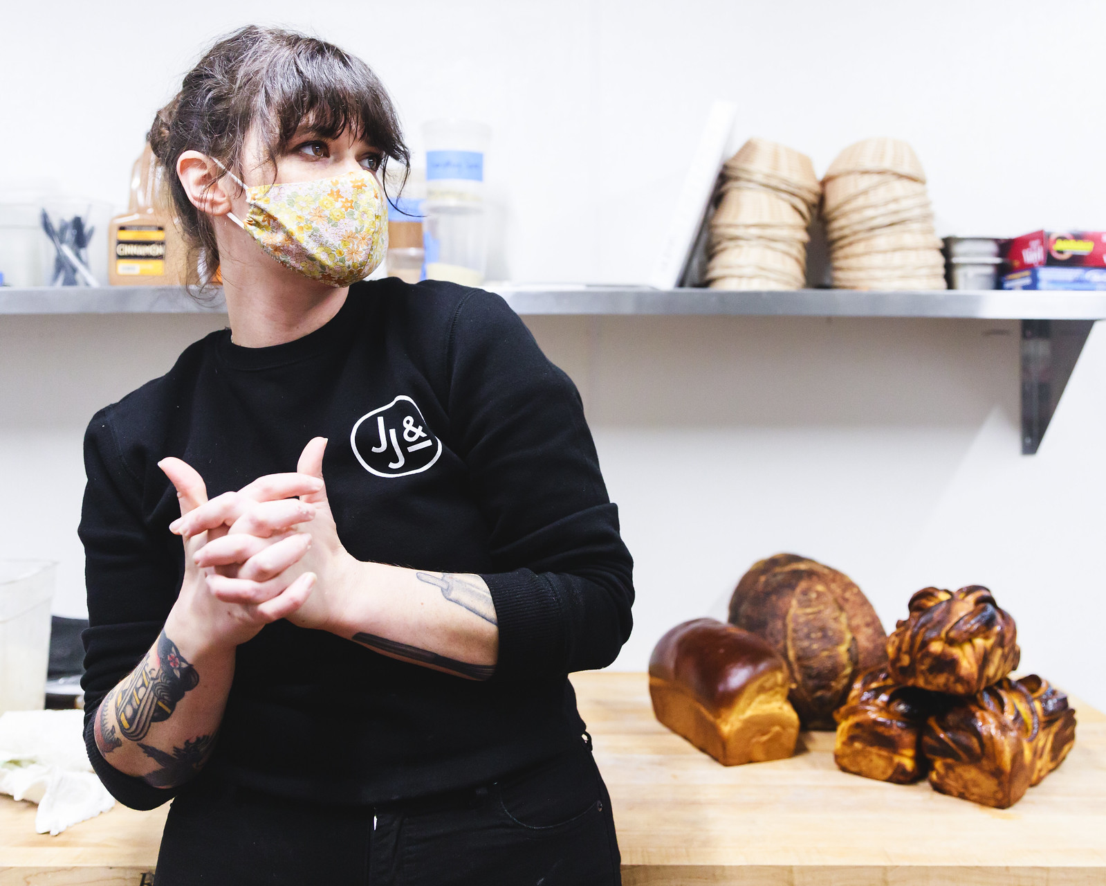 A masked baker twiddles her thumbs with bread in the background.