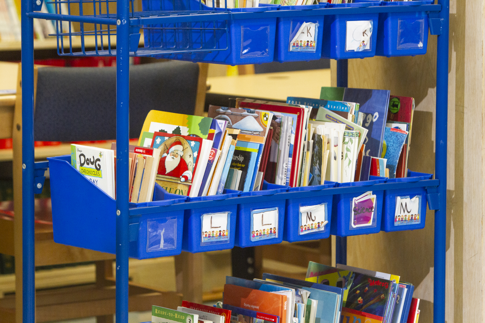 A blue cart of picture books organized alphabetically.