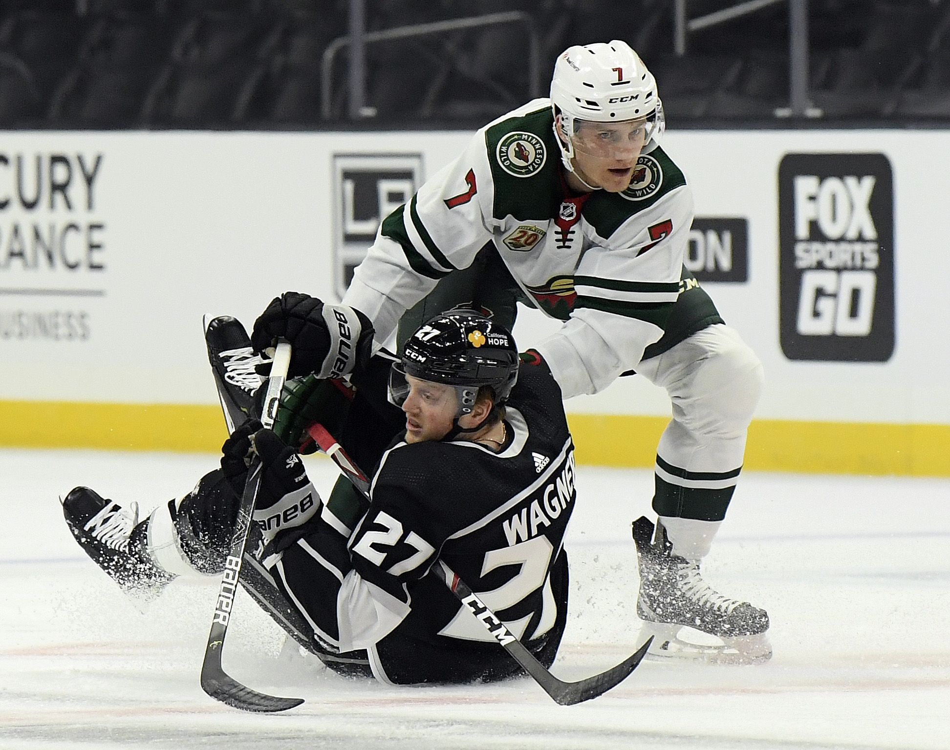 Austin Wagner #27 of the Los Angeles Kings is knocked to the ice by Nico Sturm #7 of the Minnesota Wild during the first period in the season opening game at Staples Center on January 14, 2021 in Los Angeles, California.