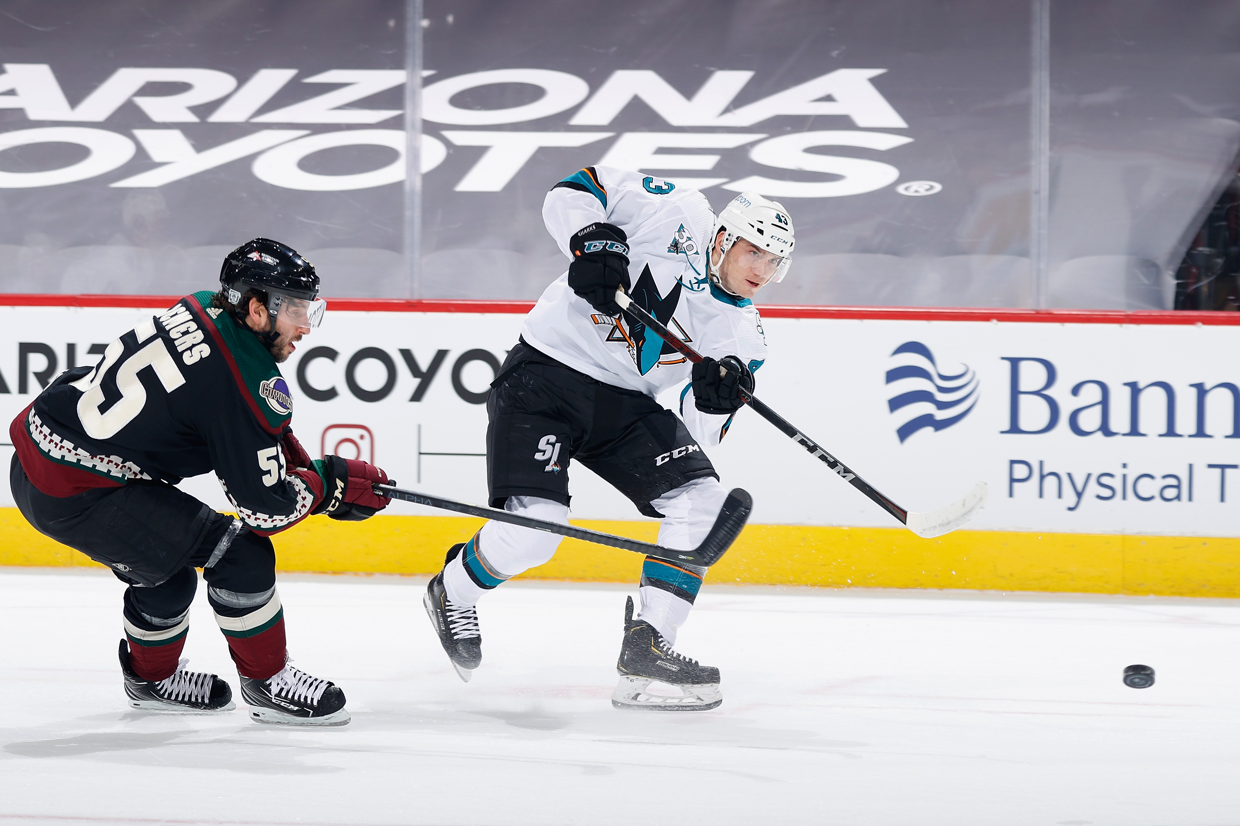 John Leonard #43 of the San Jose Sharks shoots the puck ahead of Jason Demers #55 of the Arizona Coyotes during the first period of the NHL game at Gila River Arena on January 14, 2021 in Glendale, Arizona.