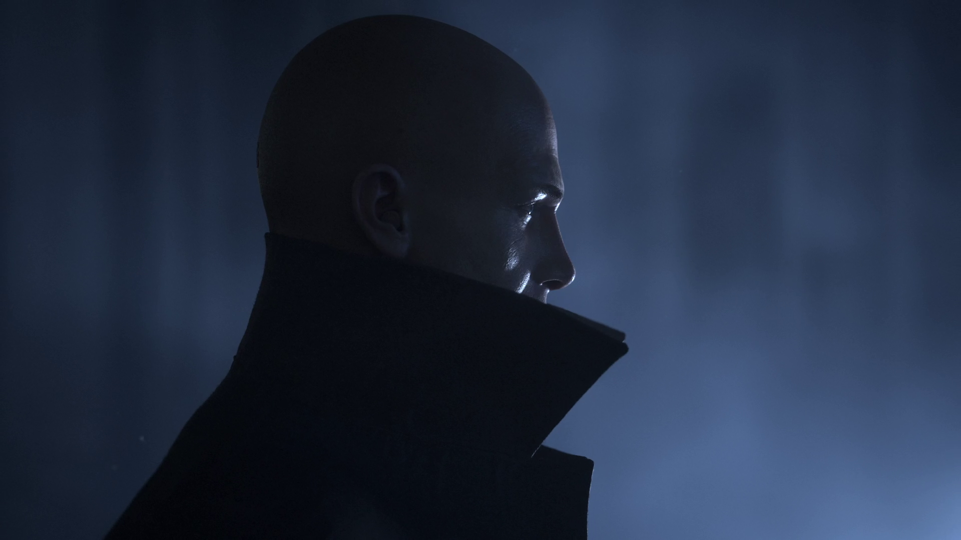 Hitman 3 - Agent 47 in profile, wearing a high collared coat. He's backed by an ominous looking blue light.