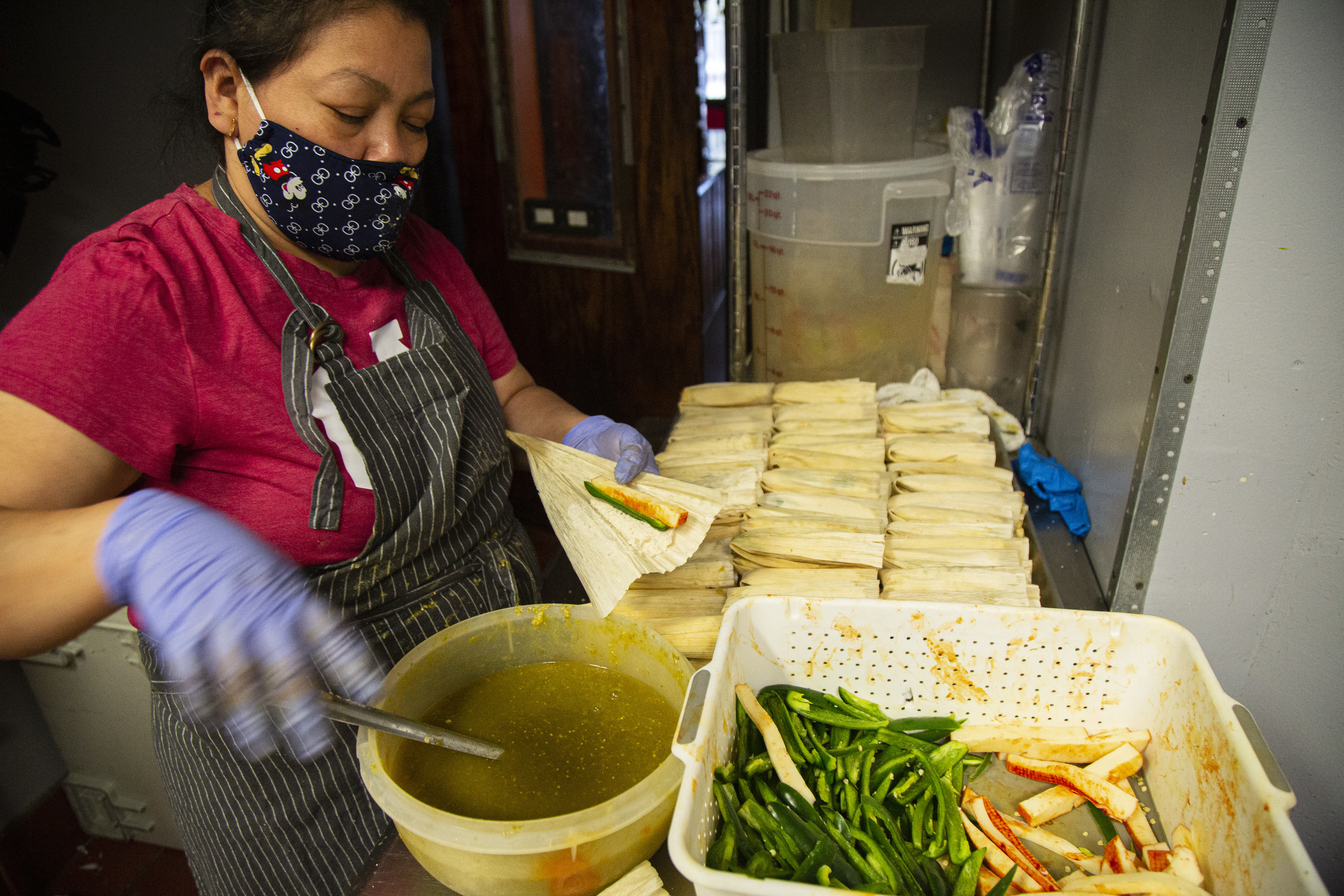 An employee adds sauce and peppers and cheese to tamale dough at restaurant Tamale Guy at 2018 W. Chicago Avenue in Ukrainian Village last year during the coronavirus shutdown.