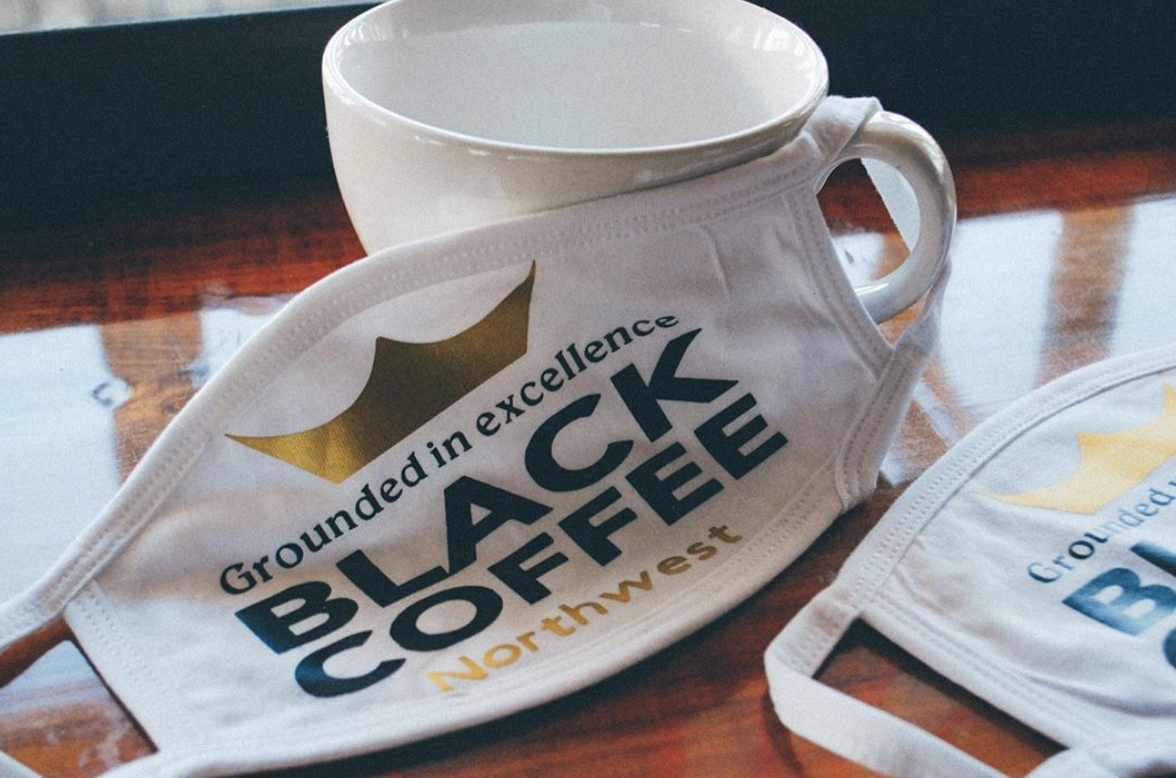 """A face mask with """"Black Coffee NW"""" written on it next to an empty coffee mug"""