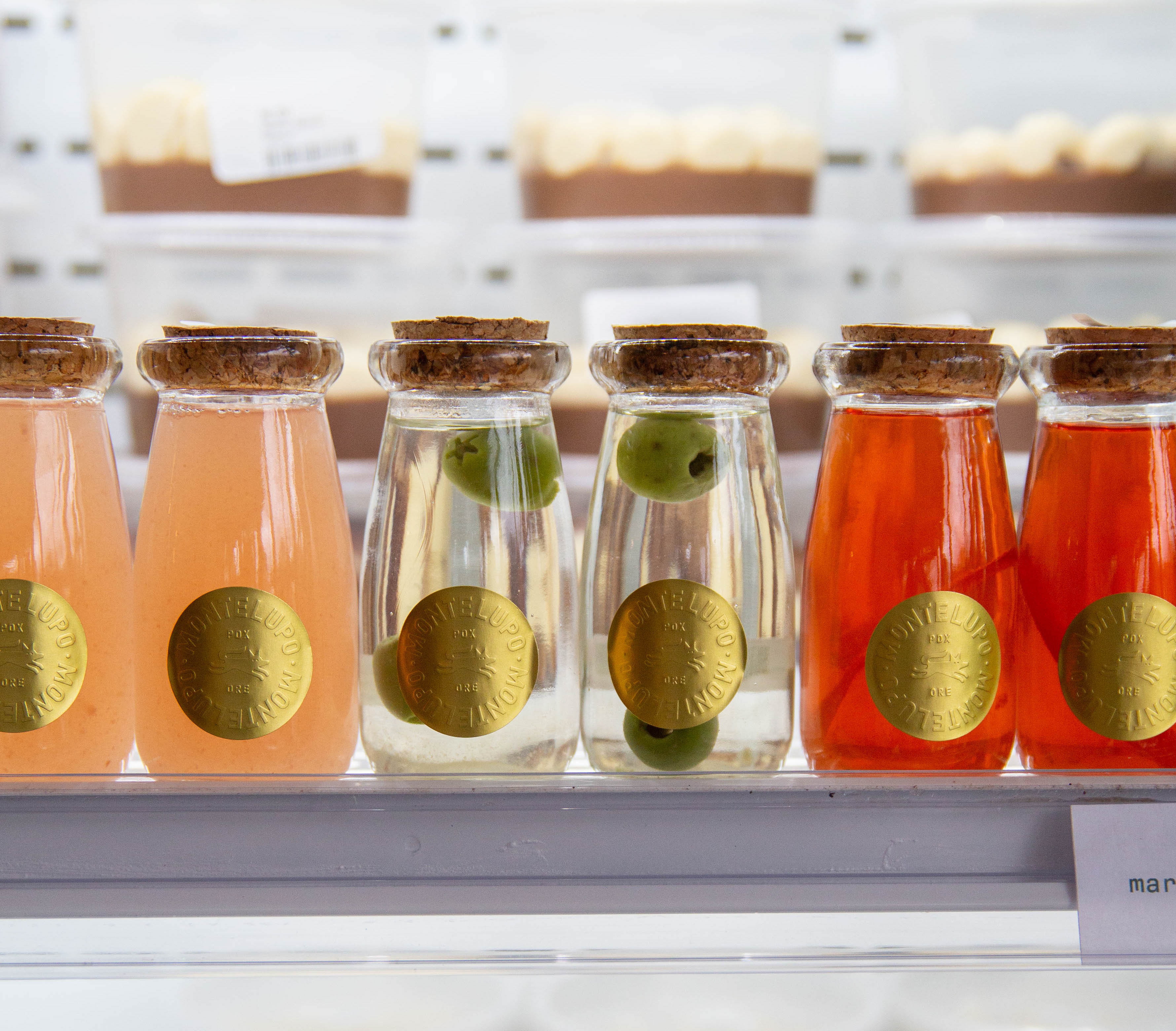 A cooler case has six short, stoppered jars. Two have a orange margarita, two have a martini with a single olive, and two are the bright red of a negroni.