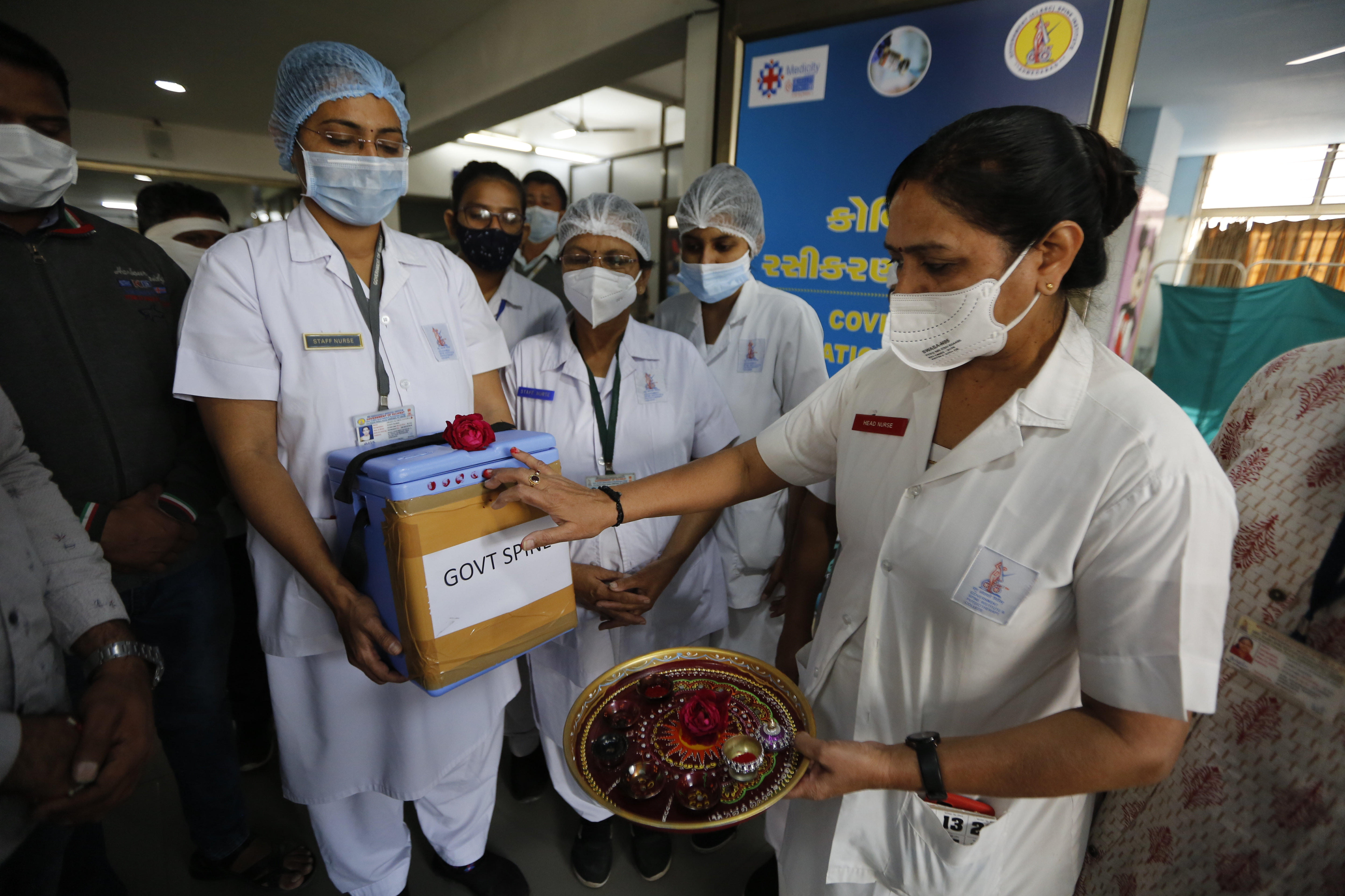 A nurse, right, performs rituals to a box containing COVID-19 vaccines upon its arrival at a government Hospital in Ahmedabad, India, on Saturday.