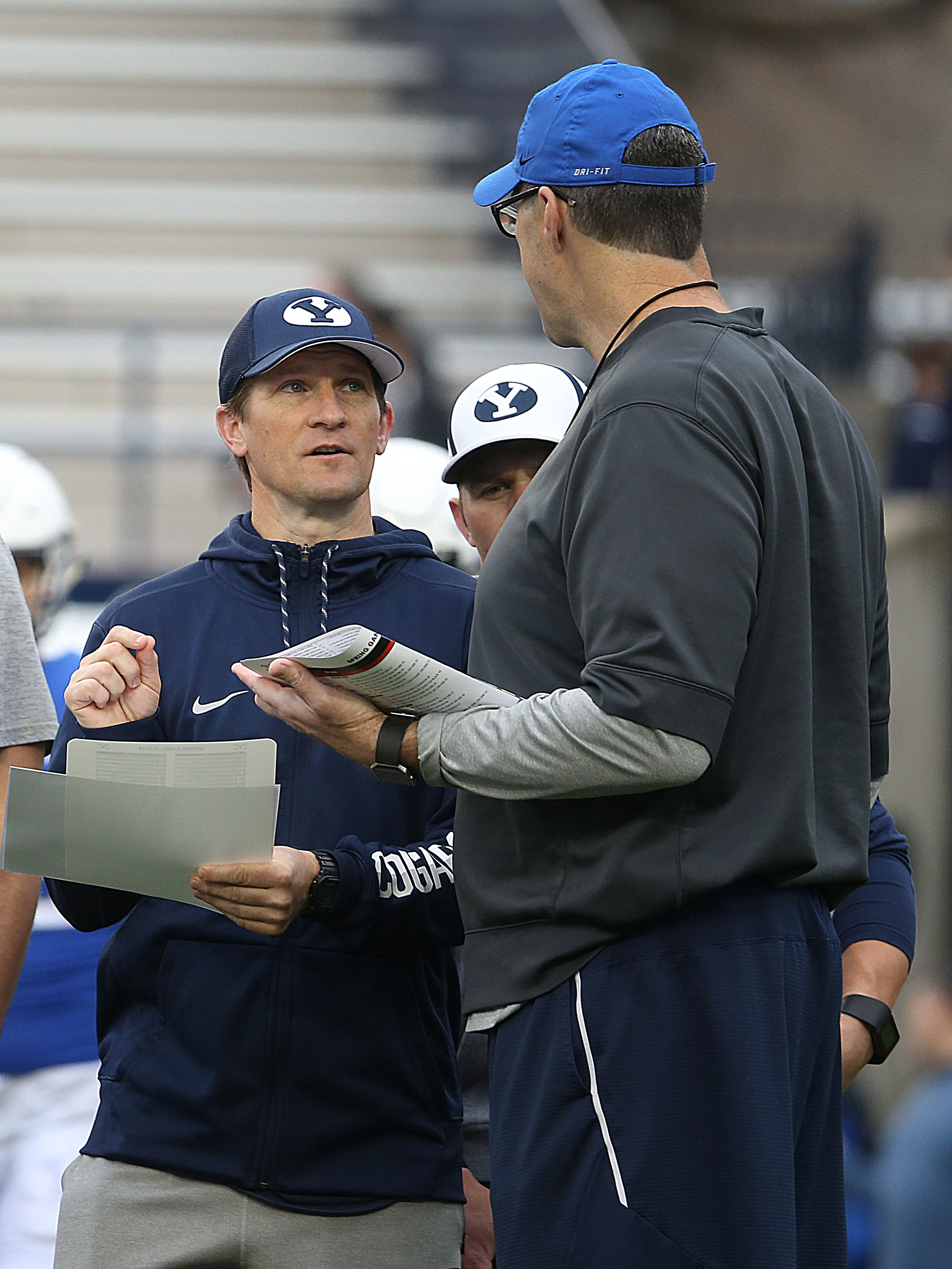 QB coach Aaron Roderick, left and offensive coordinator Jeff Grimes, right, confer during the Blue-White Game at LaVell Edwards Stadium in Provo on Saturday, April 7, 2018.