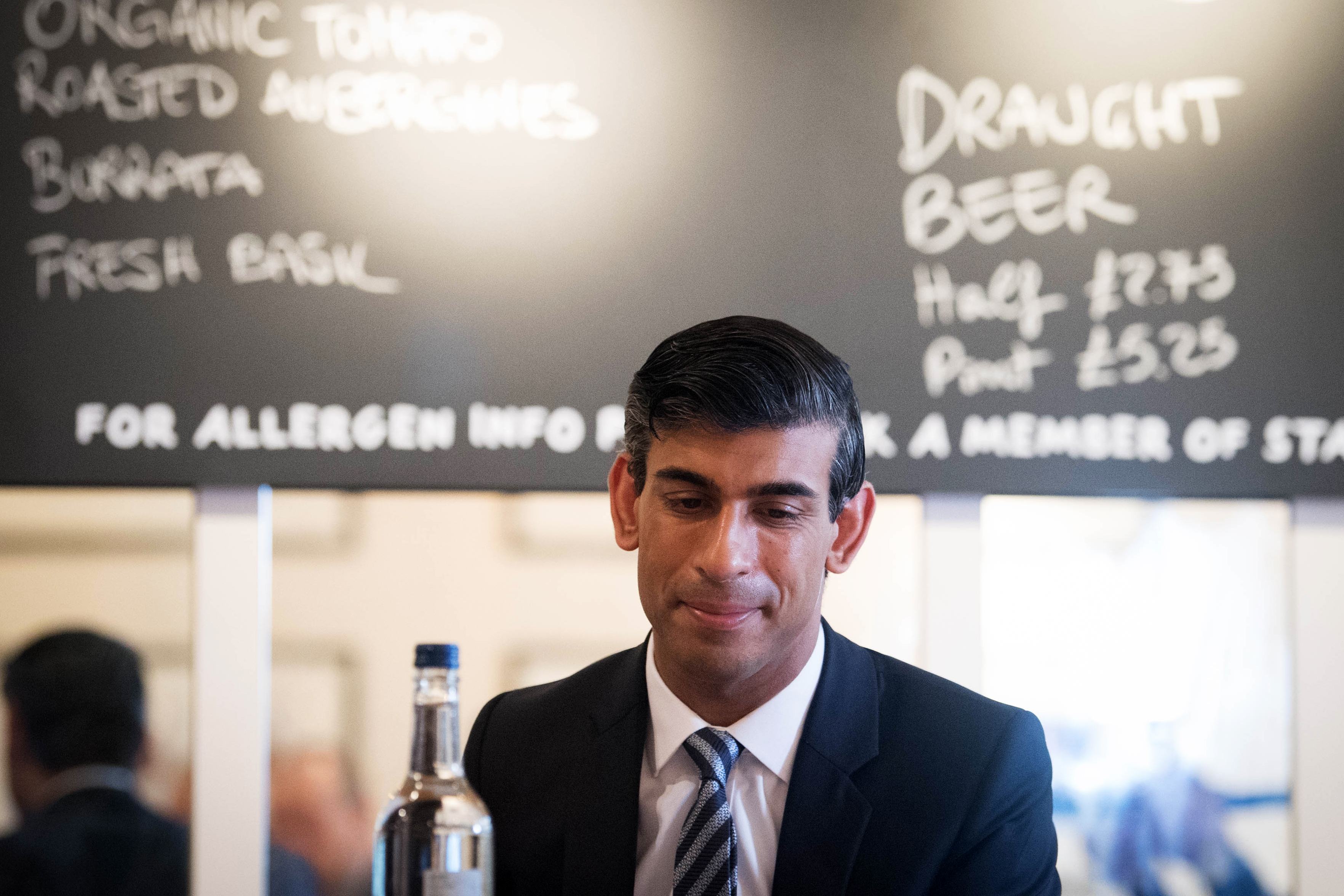 Rishi Sunak sits in front of a pizza blackboard at Franco Manca in Waterloo, London