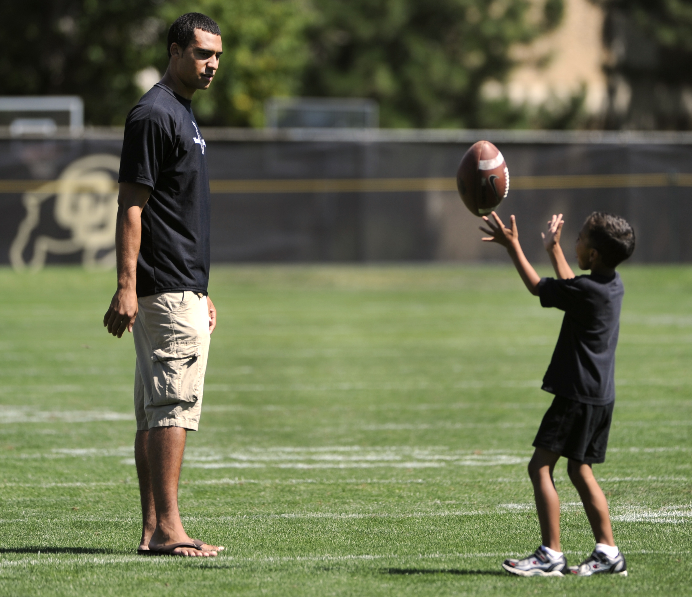 The University of Colorado Buffaloes football team has another full practice on Saturday with new and returning players and coaches getting used to the Embree system. Coach Jon Embree's son Taylor plays a little catch with cousin Sean, 5. Kathryn Scott Os
